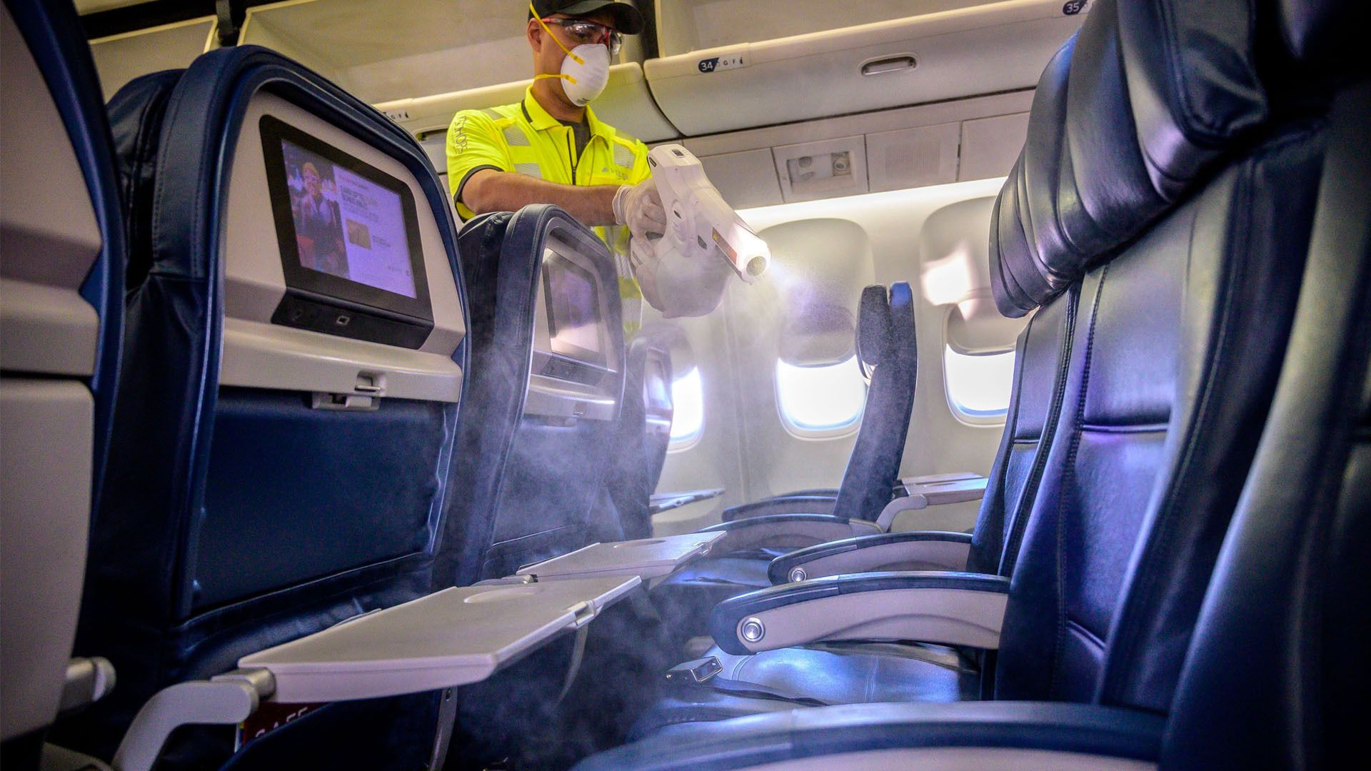 Image of Delta Air Lines worker spraying disinfectant on passenger seats.