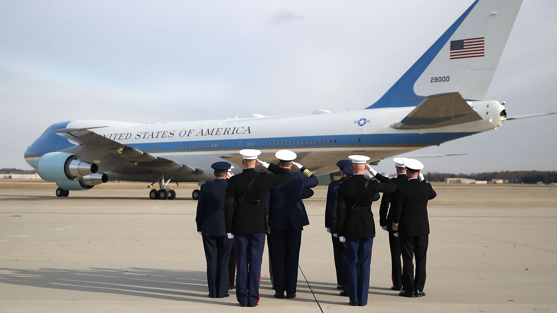 Troops salute Air Force One with George H. W. Bush casket on it.