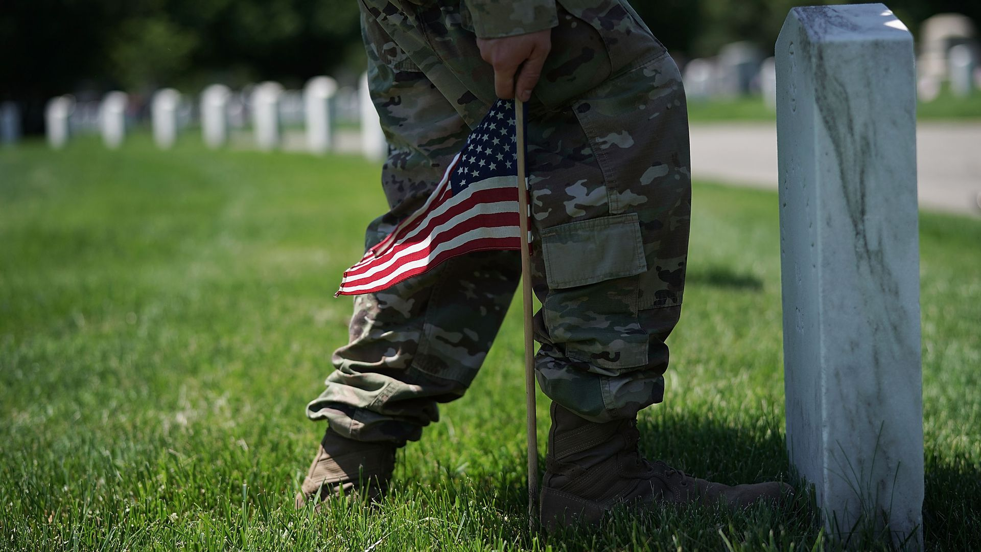 A soldier puts a small U.S. flag in the ground next to a headstone.