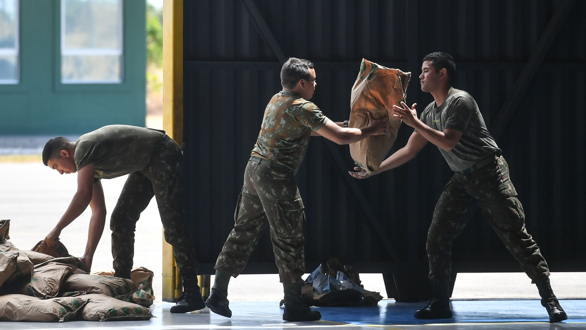 Brazilian soldiers organize sacks of powdered milk that are part of the humanitarian aid for Venezuela