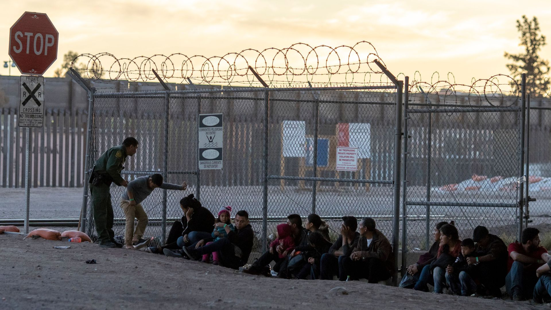 Migrants sitting against a chained link fence while one border patrol officer speaks to them.