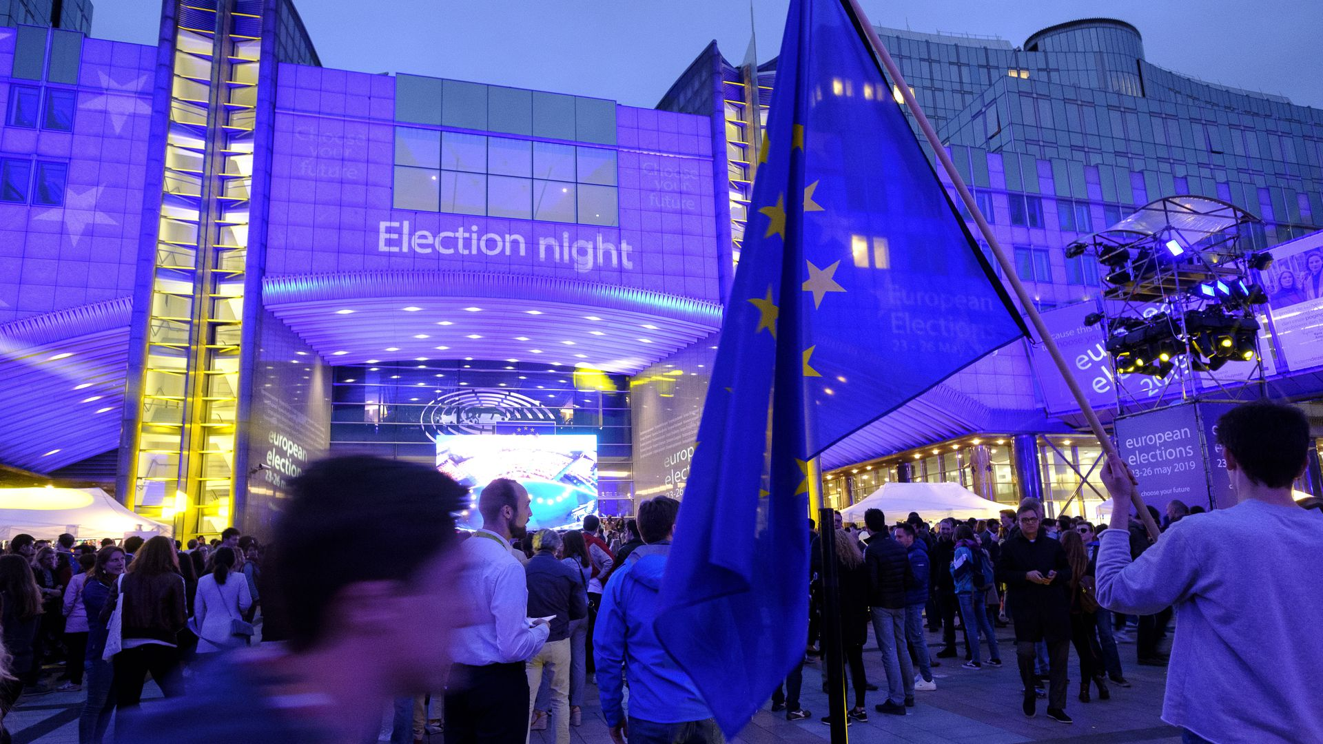 EU citizens are seen outside the European Parliament building at dusk in Brussels.