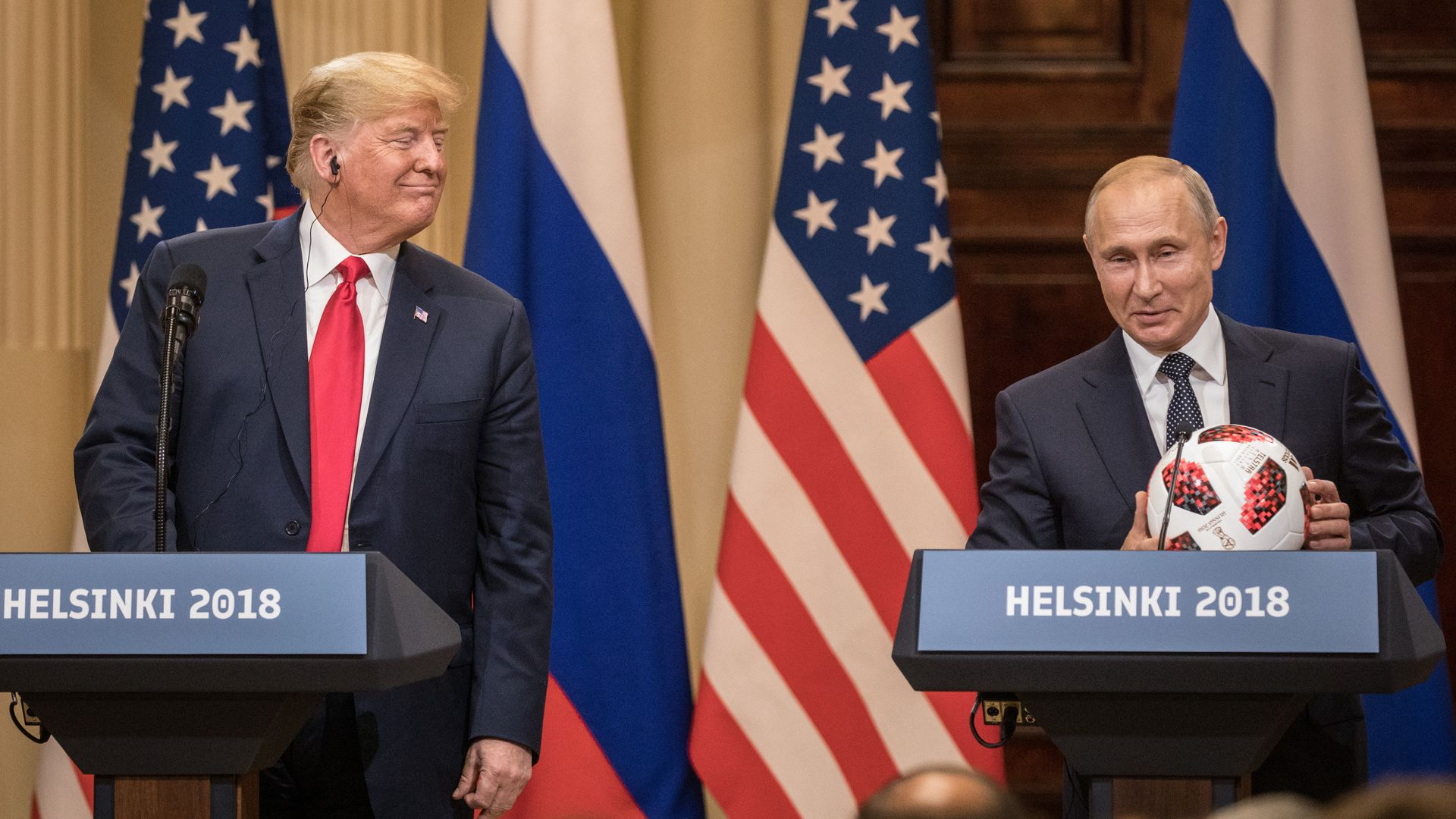 Russian President Vladimir Putin hands U.S. President Donald Trump a World Cup football during a joint press conference after their summit on July 16, 2018, in Helsinki.