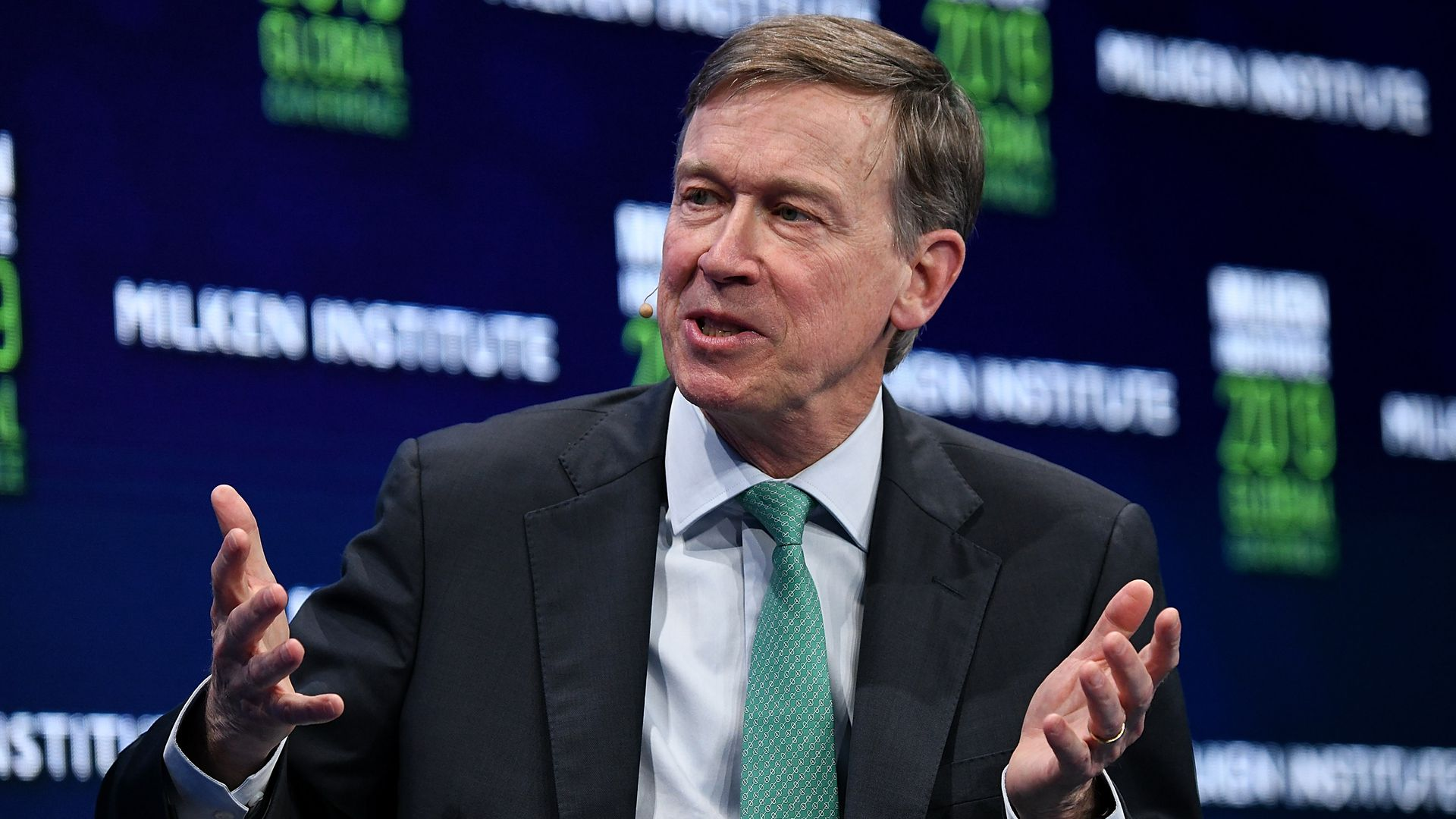 John Hickenlooper gestures during a panel discussion in California.