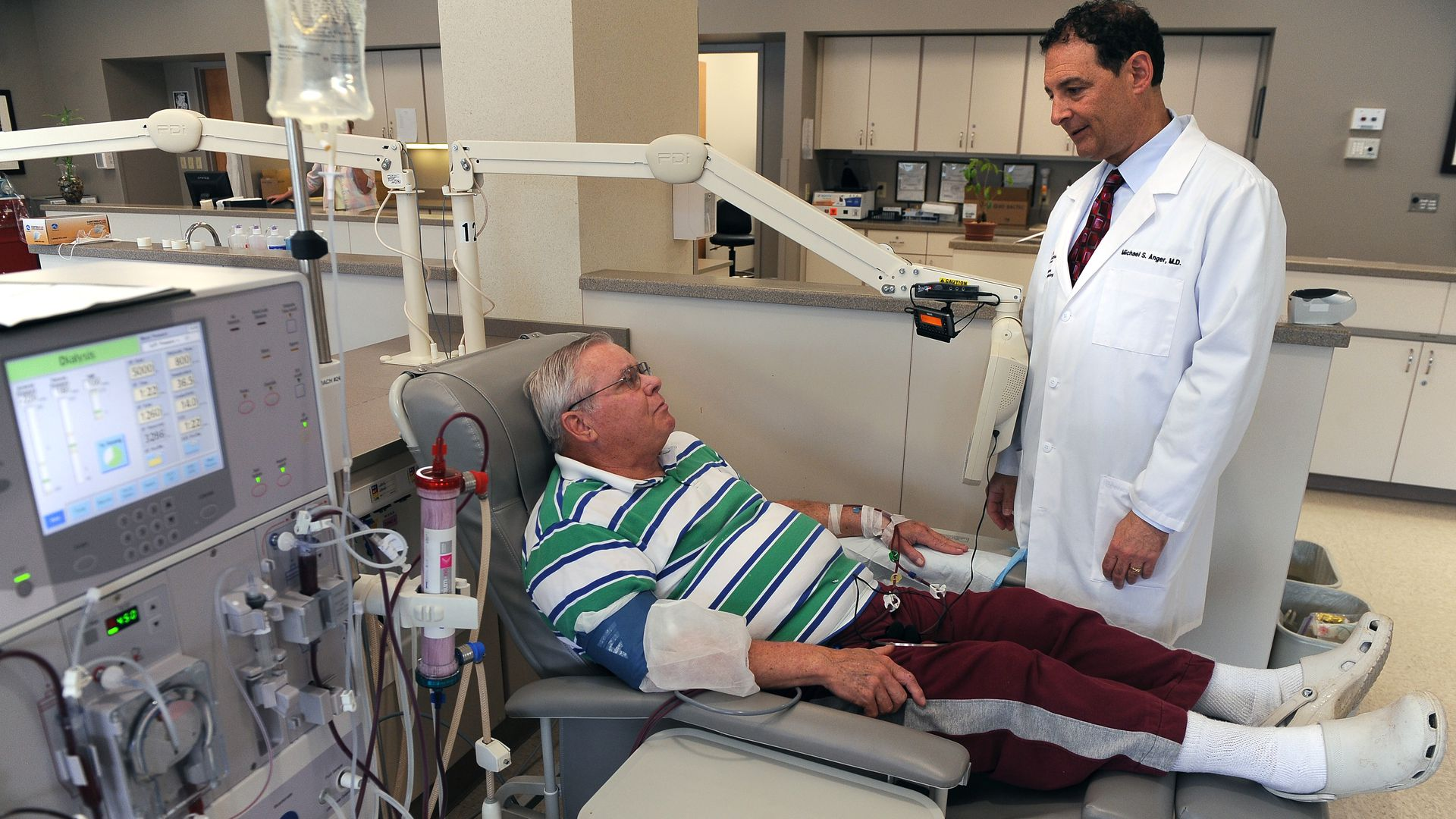 A doctor meets with a dialysis patient during treatment.