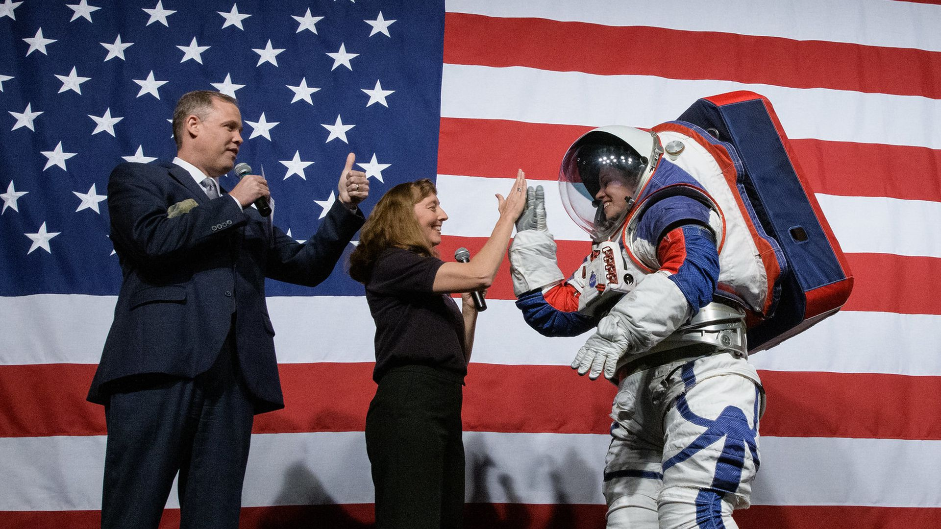 A person wears a spacesuit next to two other people in front of an American flag