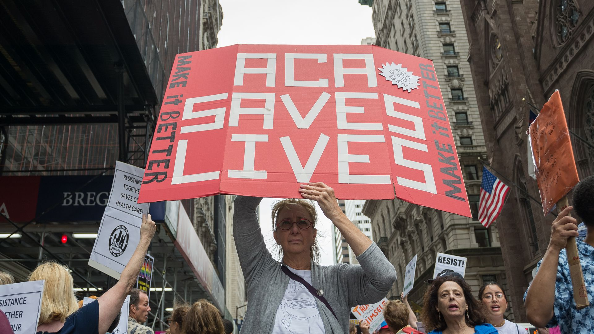 "A protester in New York holds a sign saying, ""ACA saves lives"""