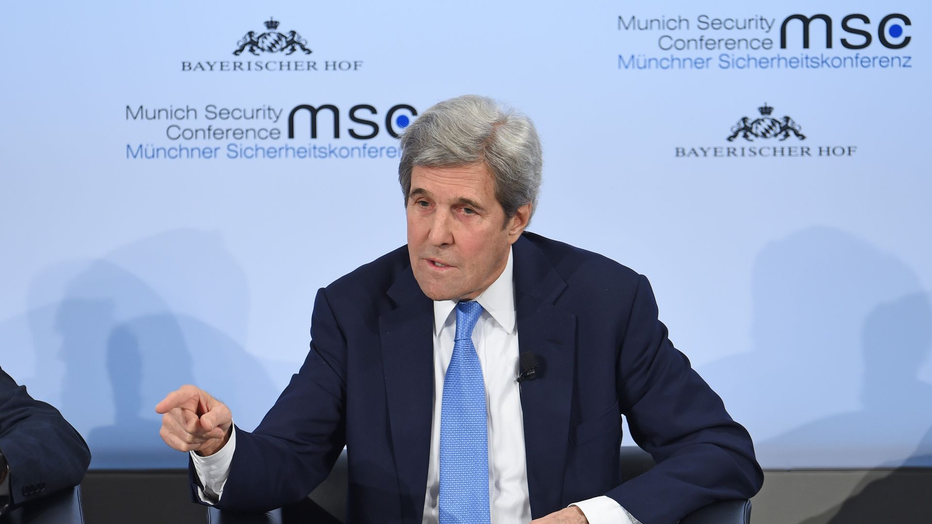 Kerry gestures while speaking, seated, on stage