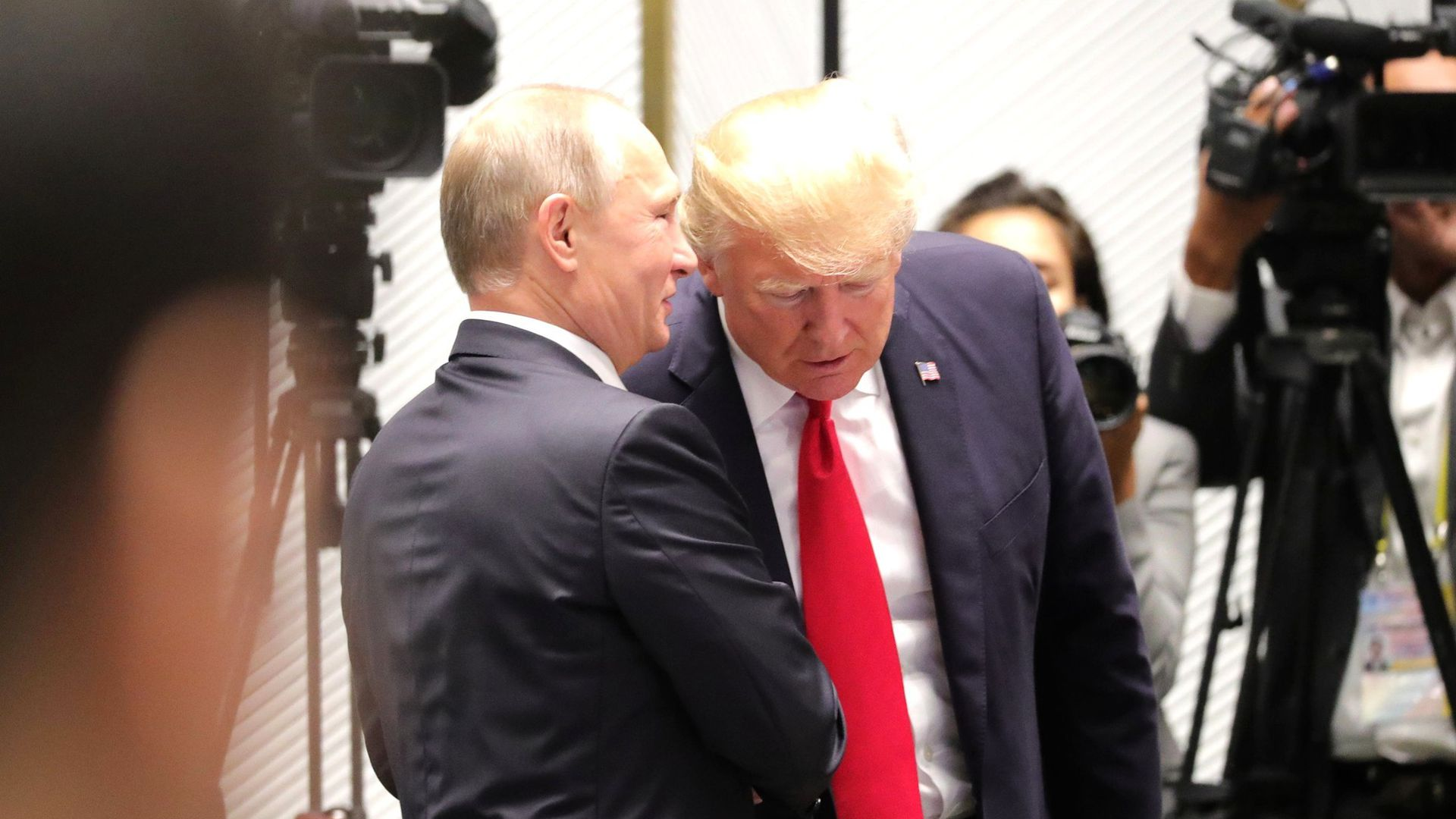 Trump and Putin shake hands as Putin says something in Trump's ear