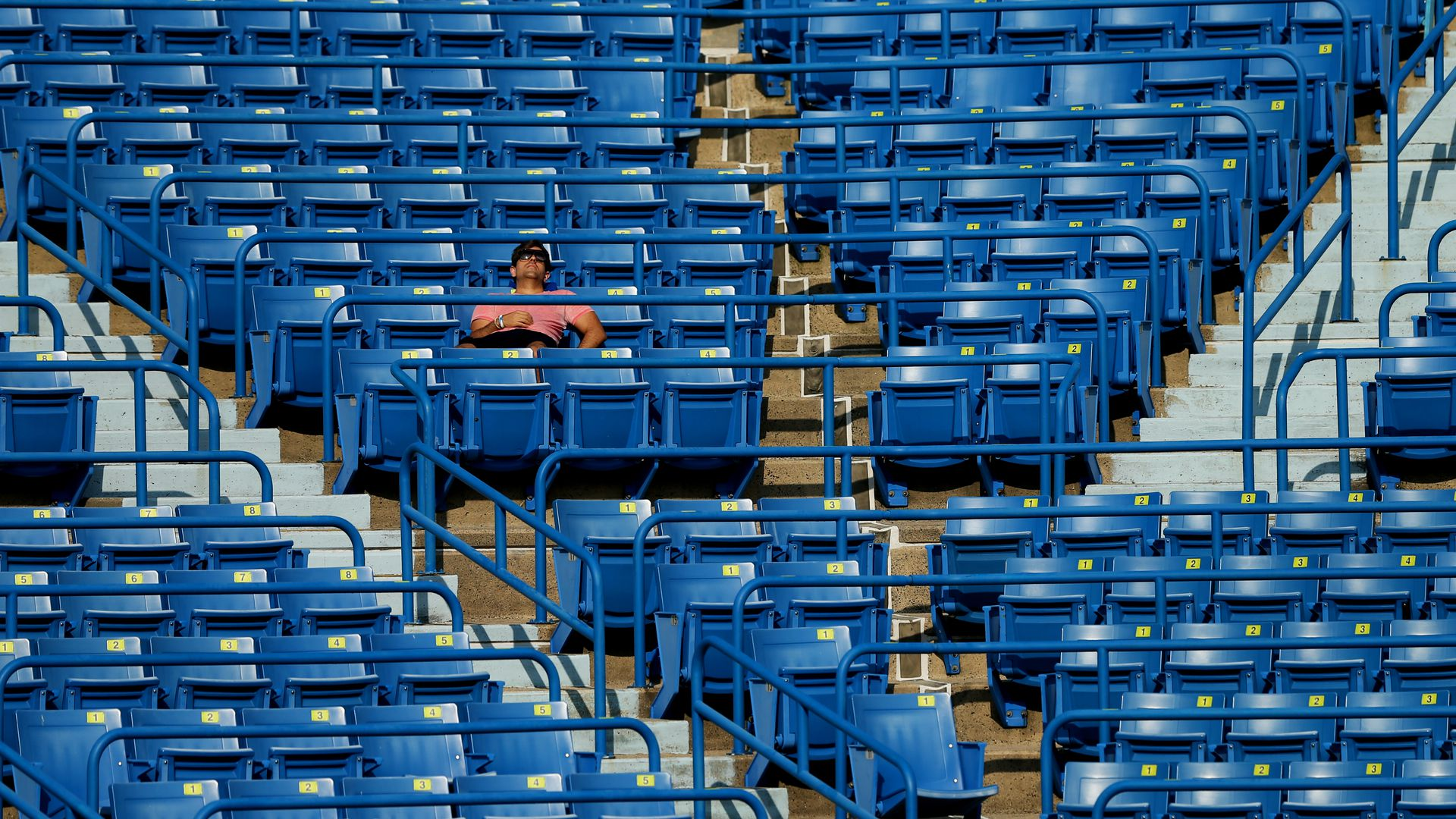 A man catches some Z's during a tennis match, surrounded by empty stadium seats.