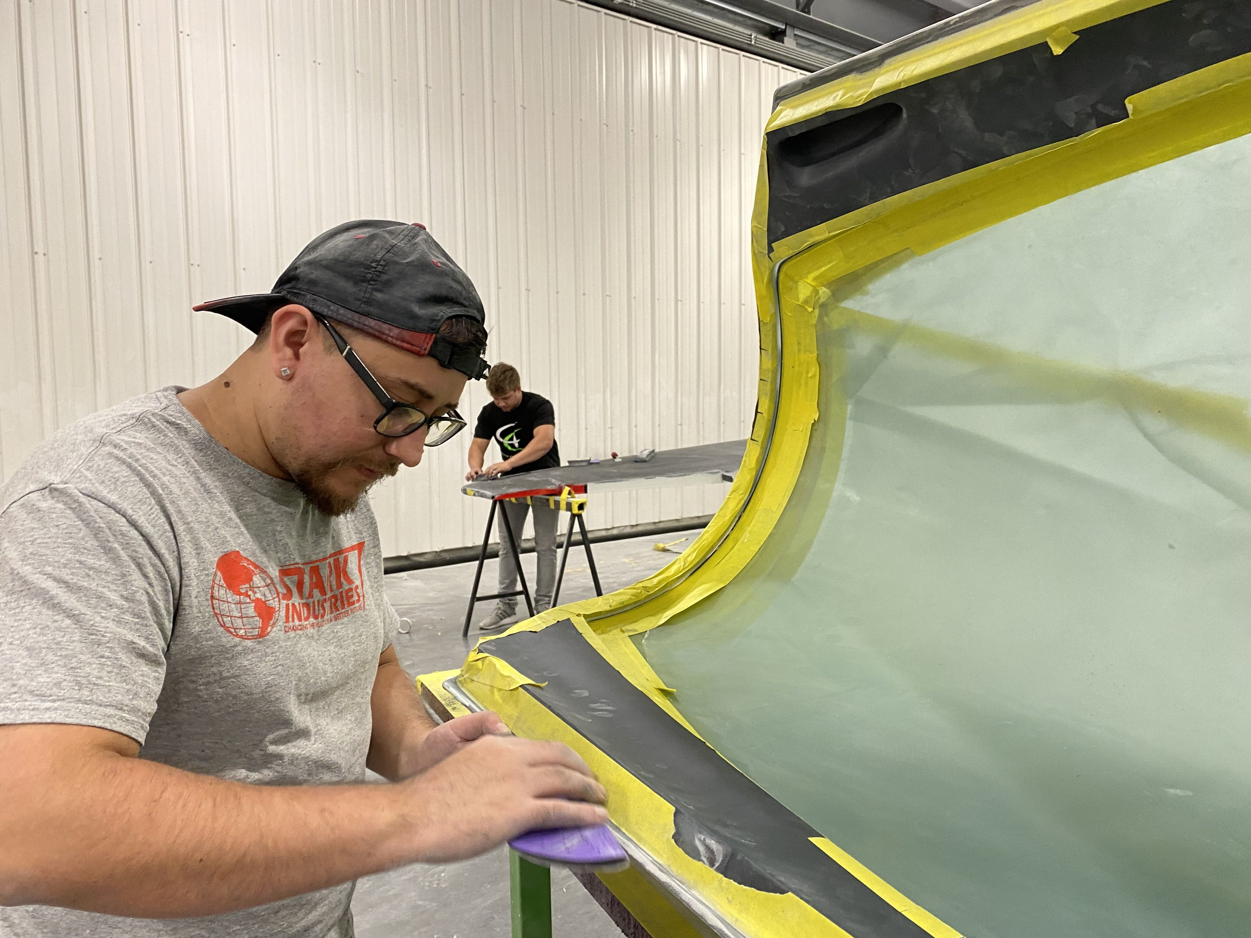A worker preps part of a plane for painting.