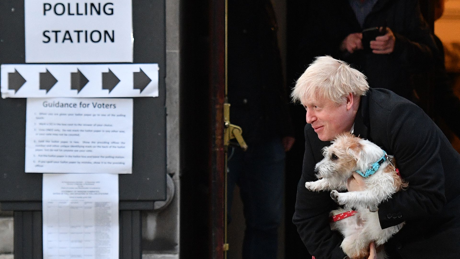 Britain's Prime Minister Boris Johnson poses with his dog Dilyn as he leaves from a Polling Station