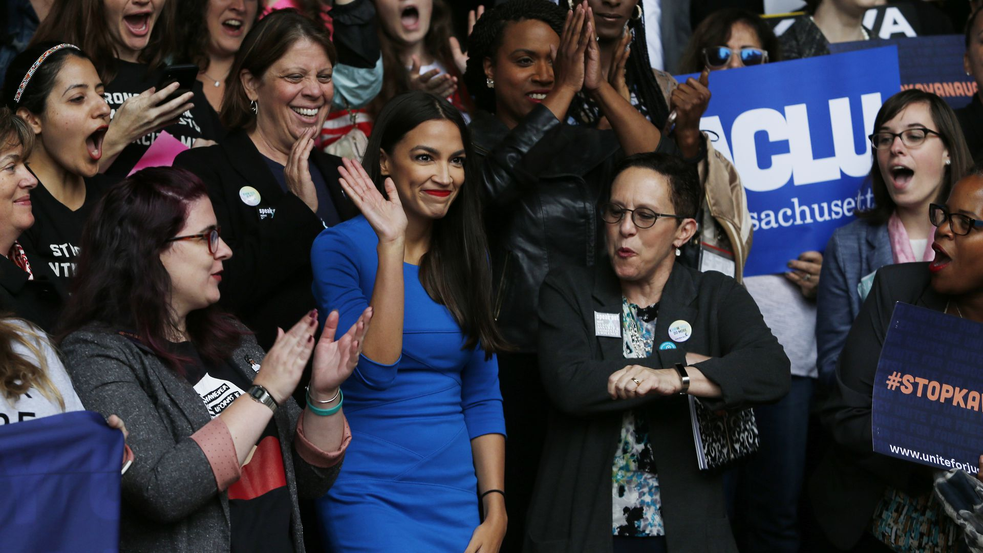 Alexandria Ocasio-Cortez waves in the midst of a crowd wearing a bright blue dress.
