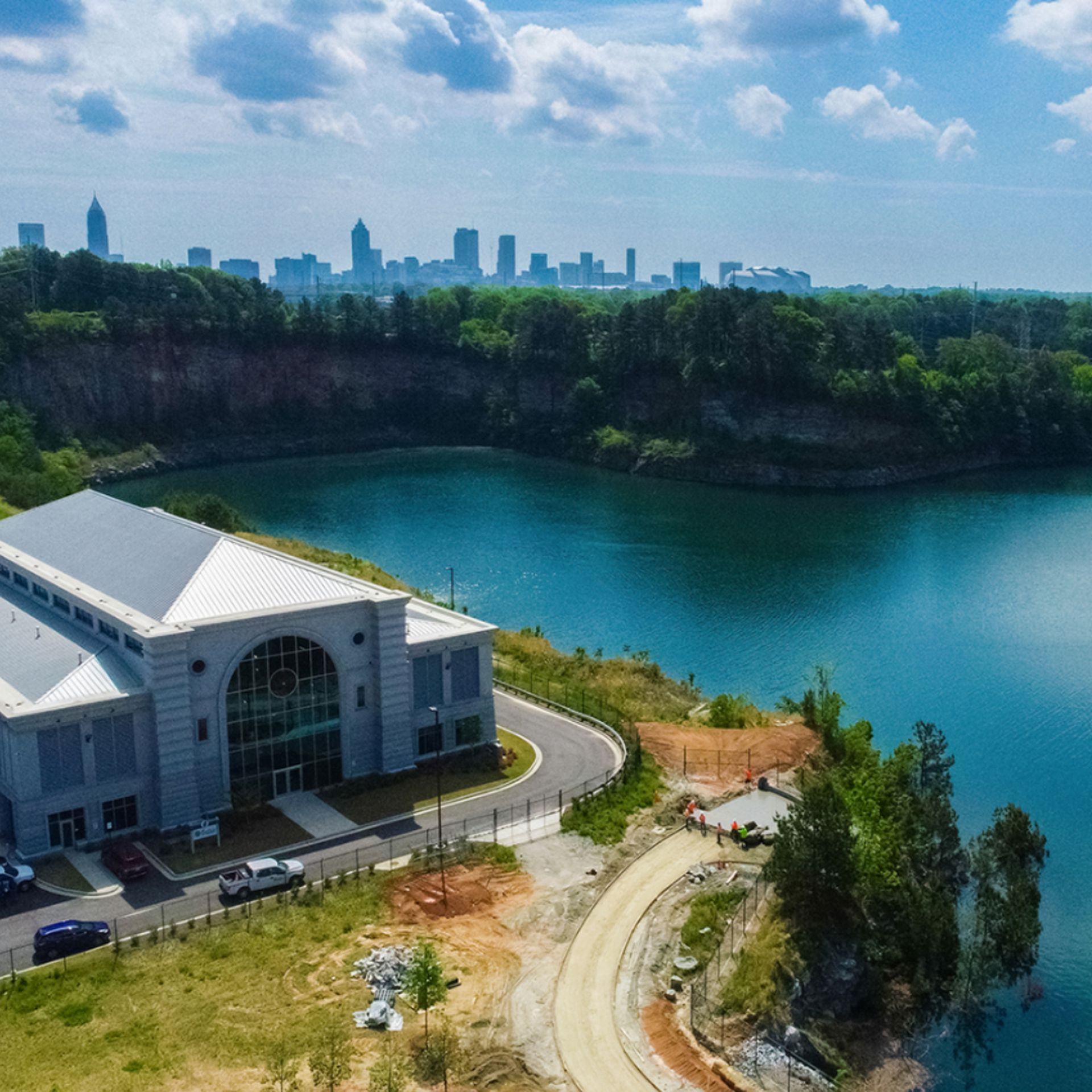A building overlooks a giant reservoir with the Atlanta skyline in the background