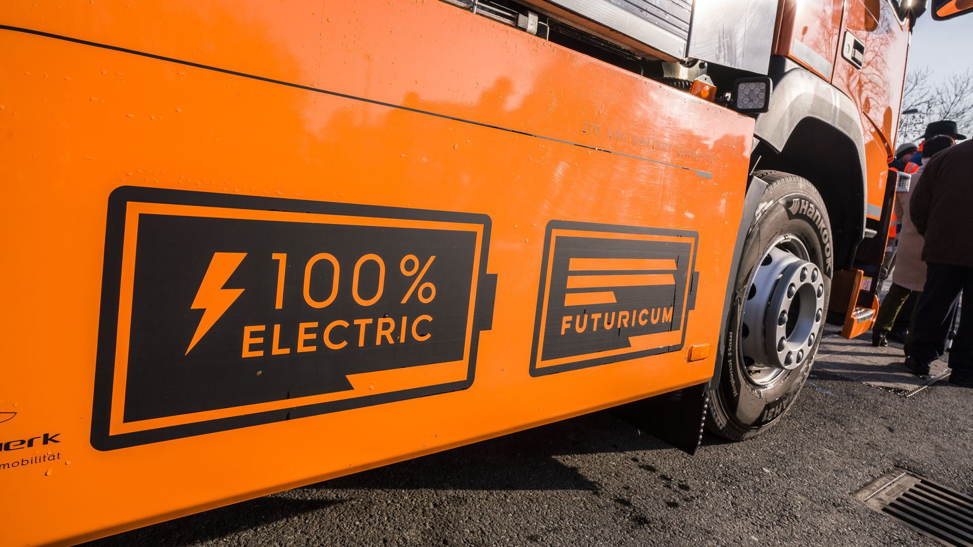 """A photo of the side of an orange electric trash truck that says """"100% electric."""""""