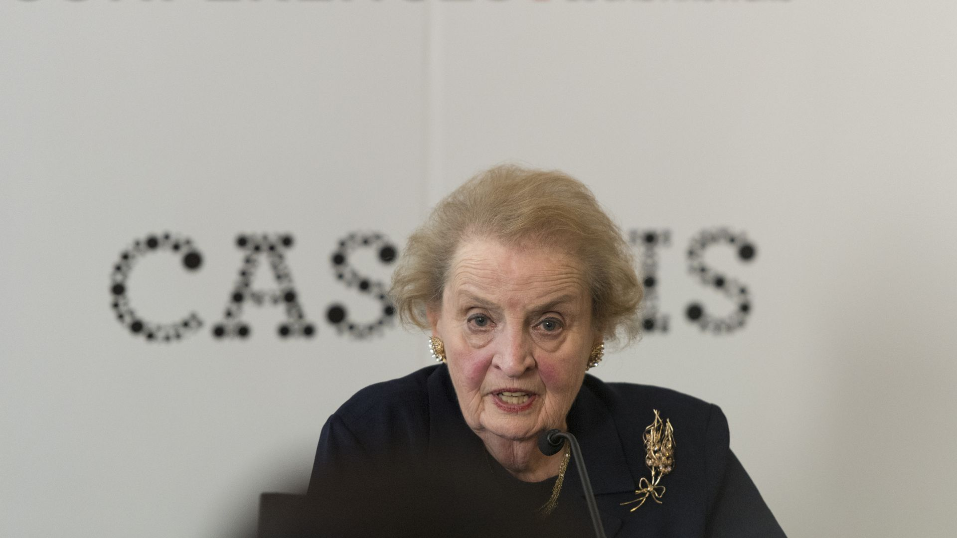 Madeleine Albright in black before a white background with black lettering.