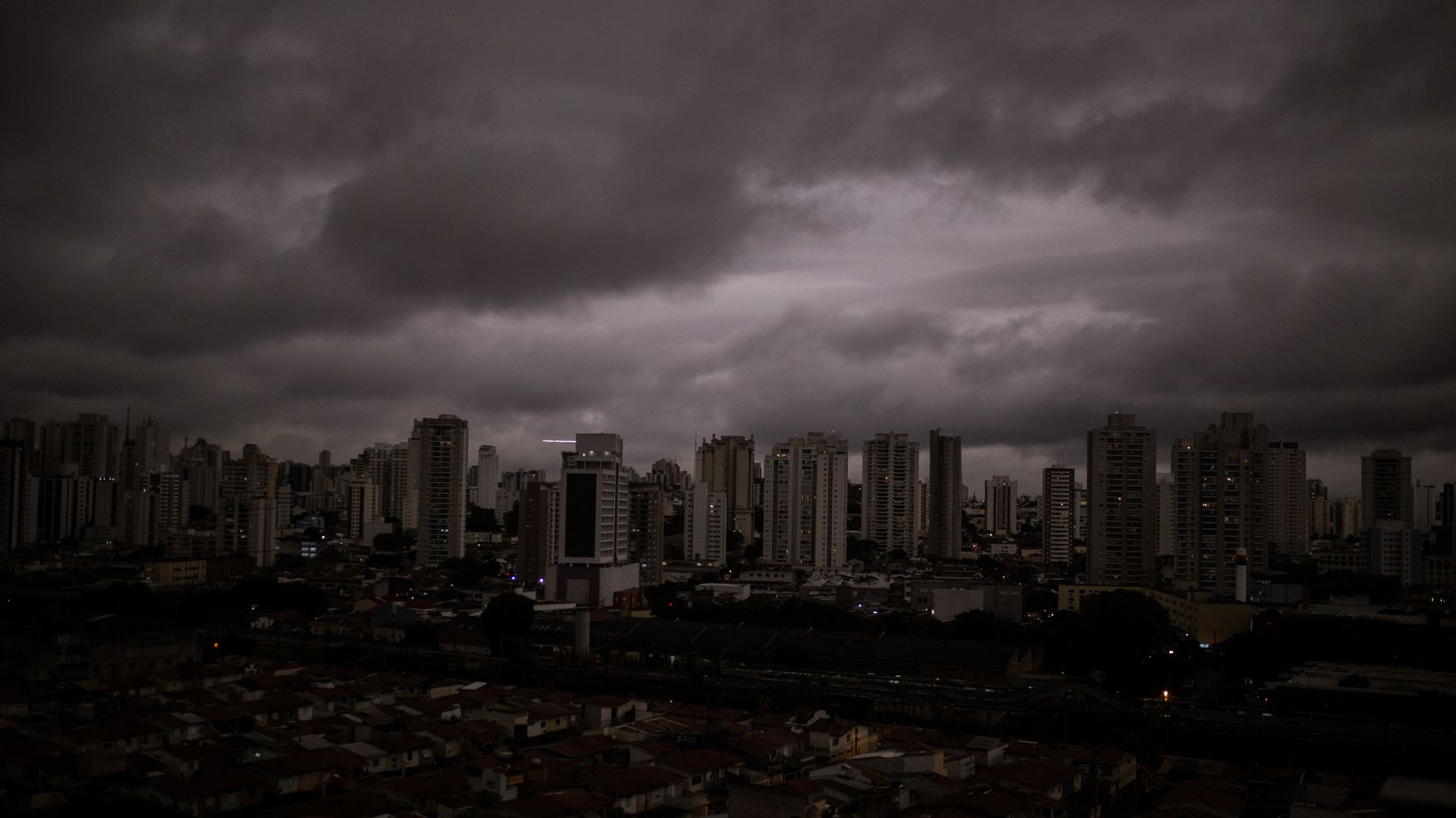 In this image, a darkened and cloudy skyline is seen over a dark city