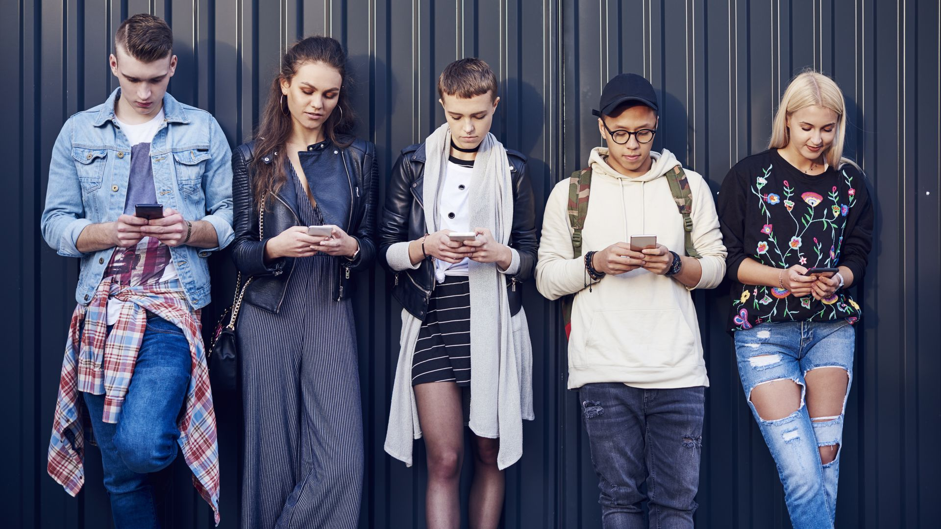 In this image, five fashionably dressed young adults look at their phones while standing in a line against a wall.