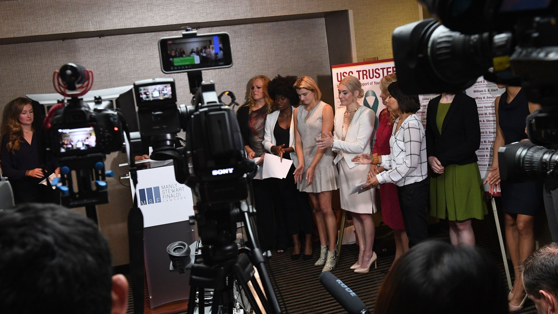 A group of young women stand in front of cameras.