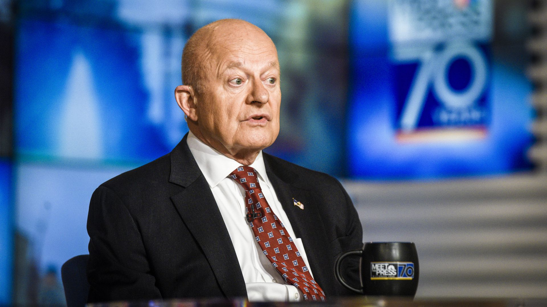 James Clapper sitting at a desk on a TV set with his eyes wide open