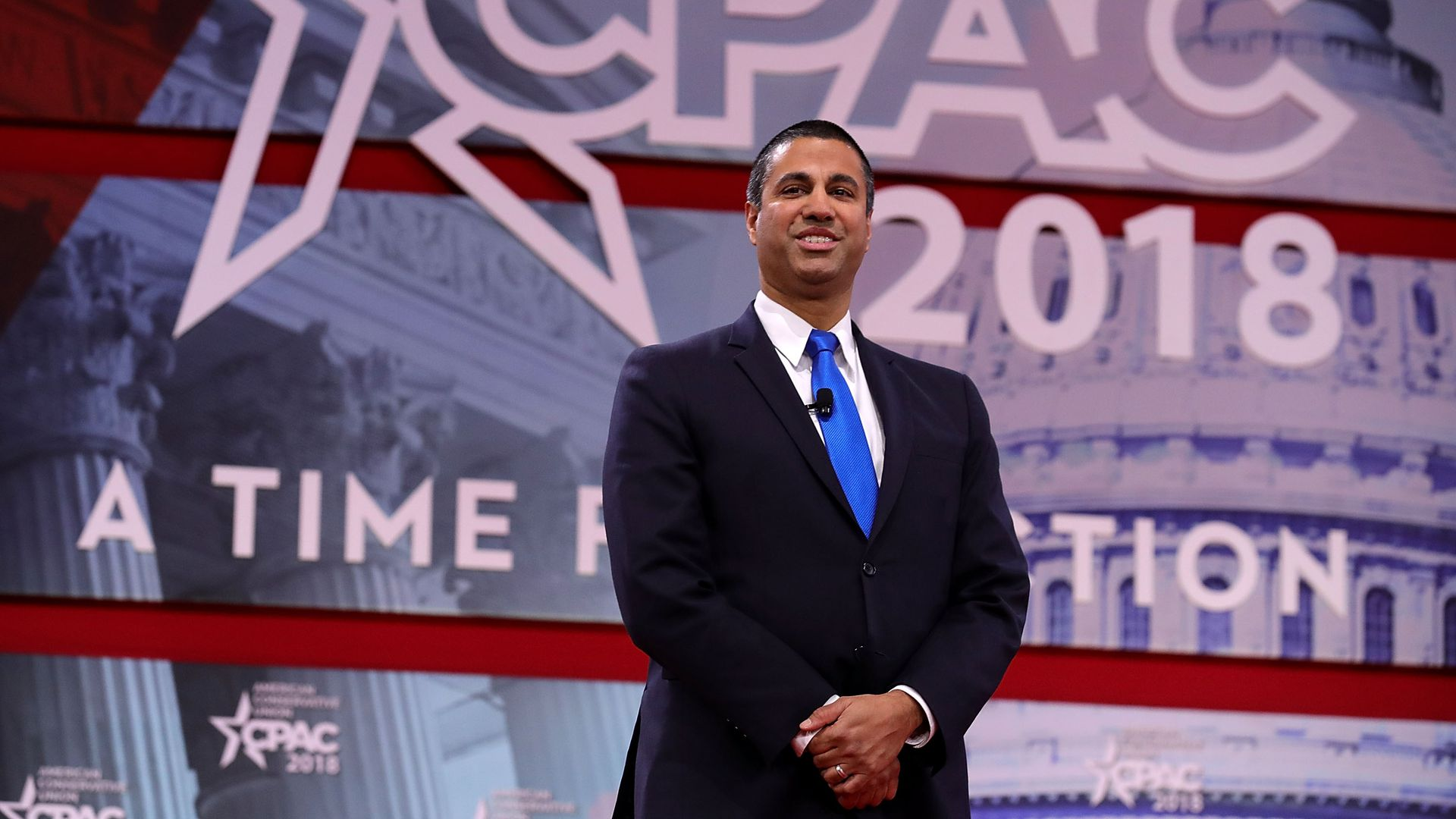 Ajit Pai stands in front of a CPAC sign with his hands clasped