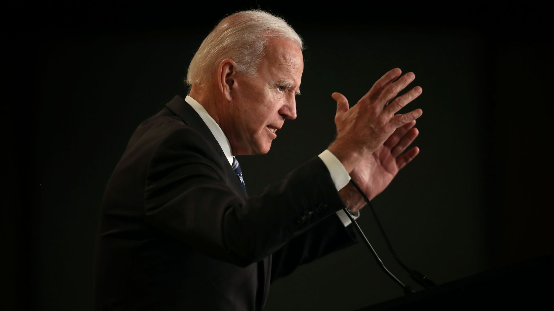 In this image, Biden stands with his hands outstretched.