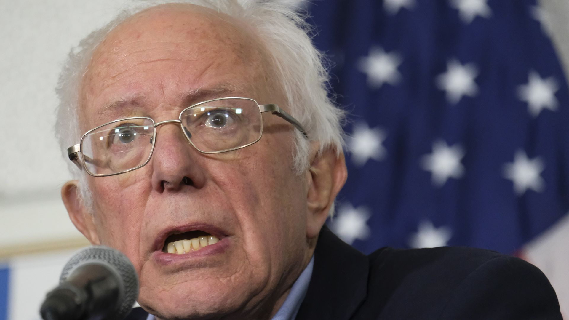 In this image, Bernie Sanders speaks into a microphone.