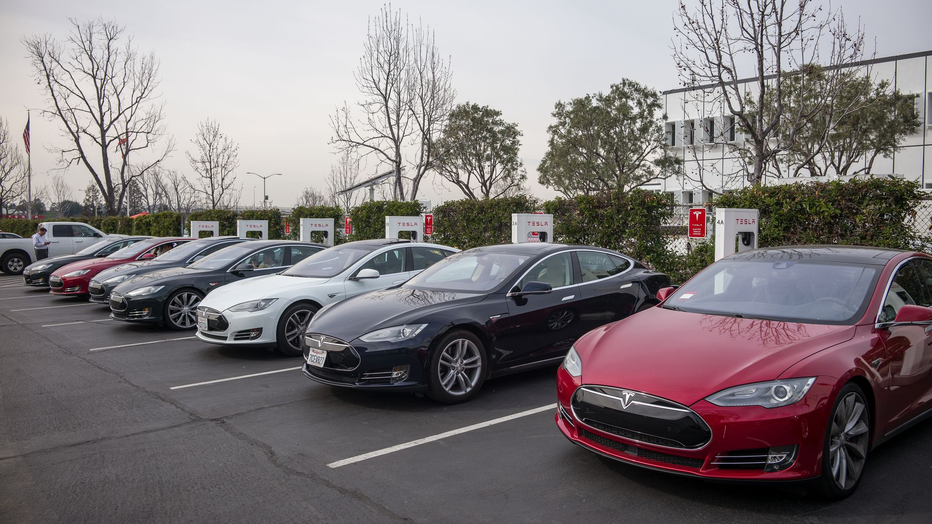 Cars charge at stations outside of Tesla's factory in Fremont