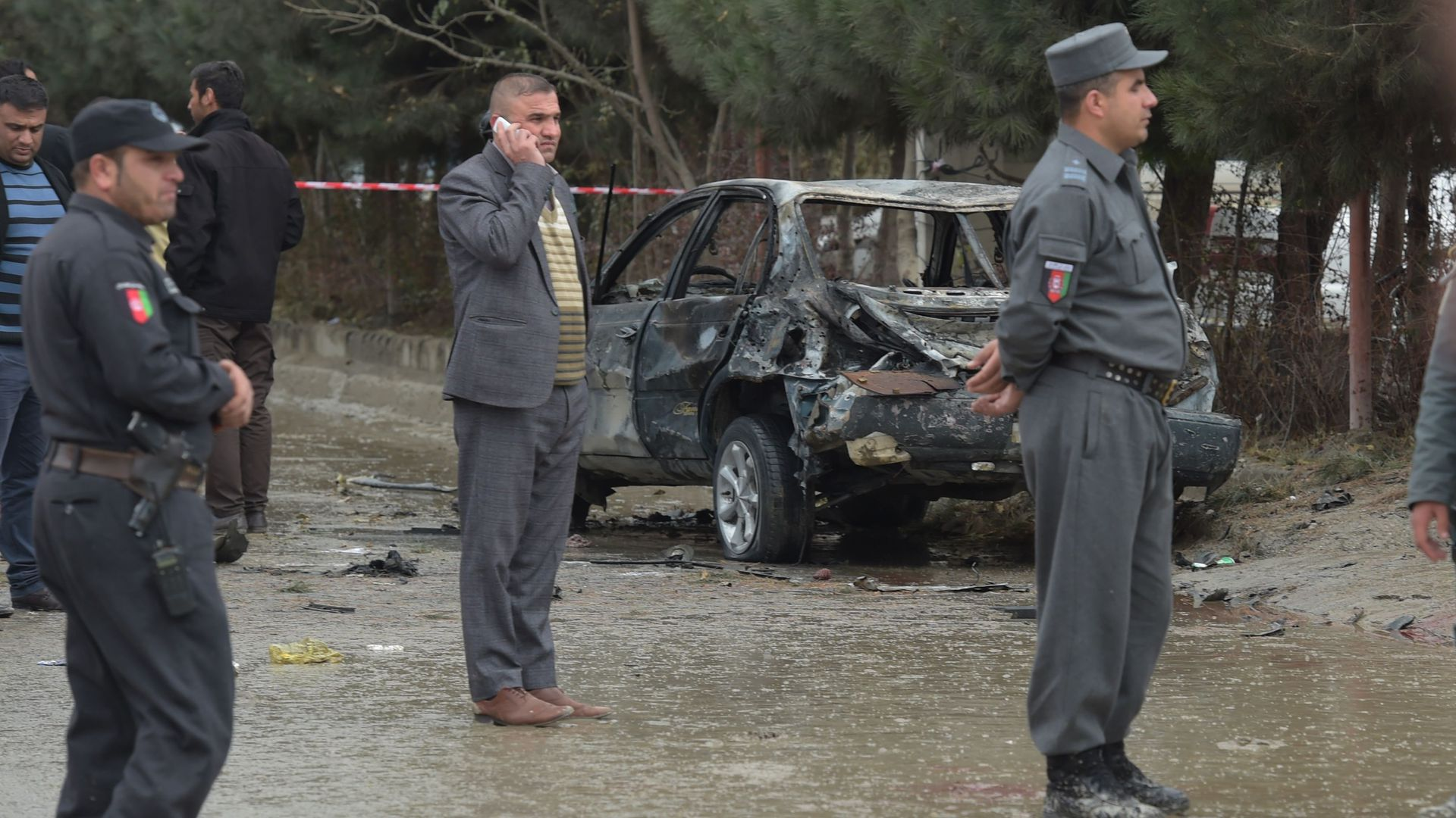 Afghan security personnel standing next to burnt-out car