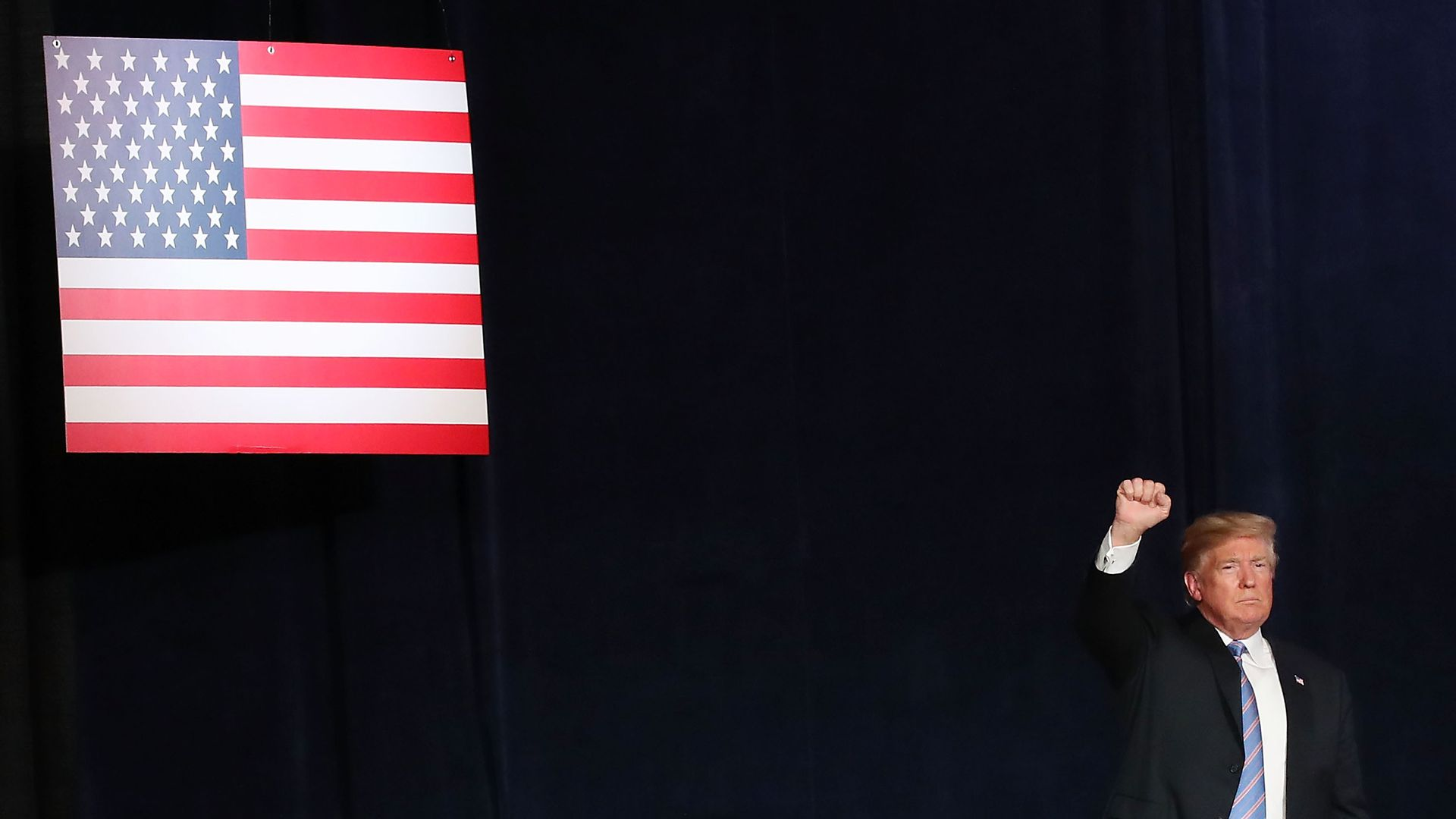 Donald Trump raises his arm in a fist before a navy blue background and an American flag.