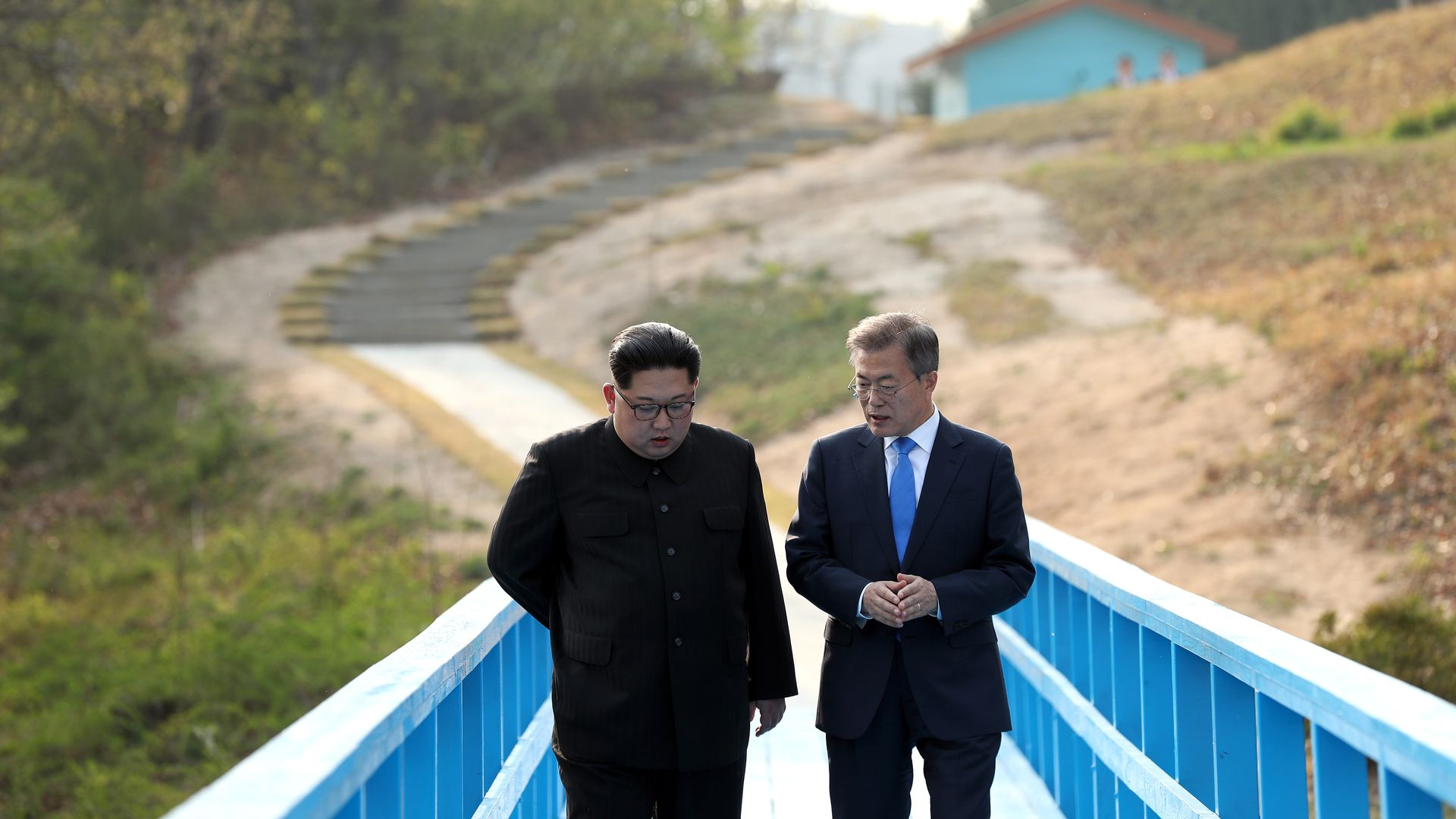 Kim Jong-un and Moon Jae-in walk down a blue bridge.