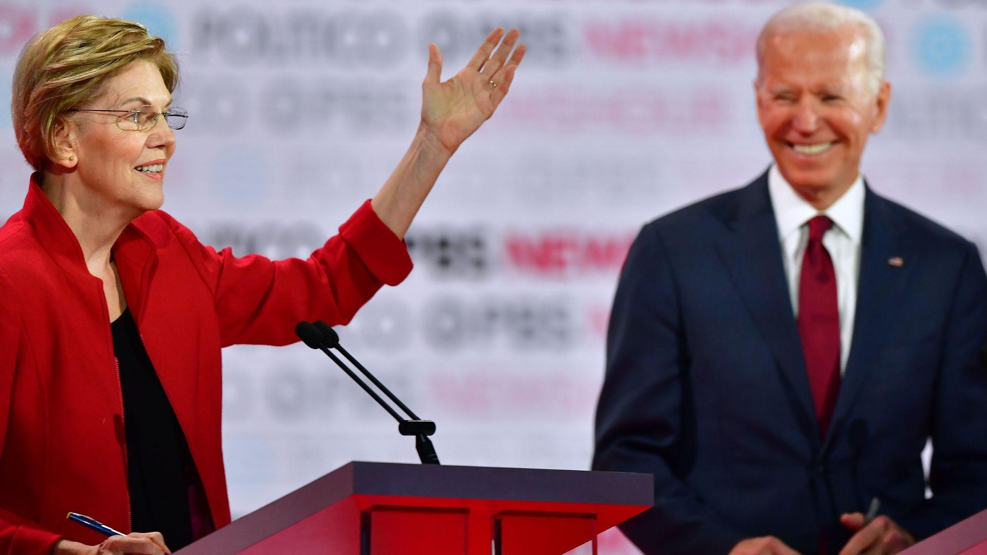 In this image, Elizabeth Warren and Joe Biden stand on stage
