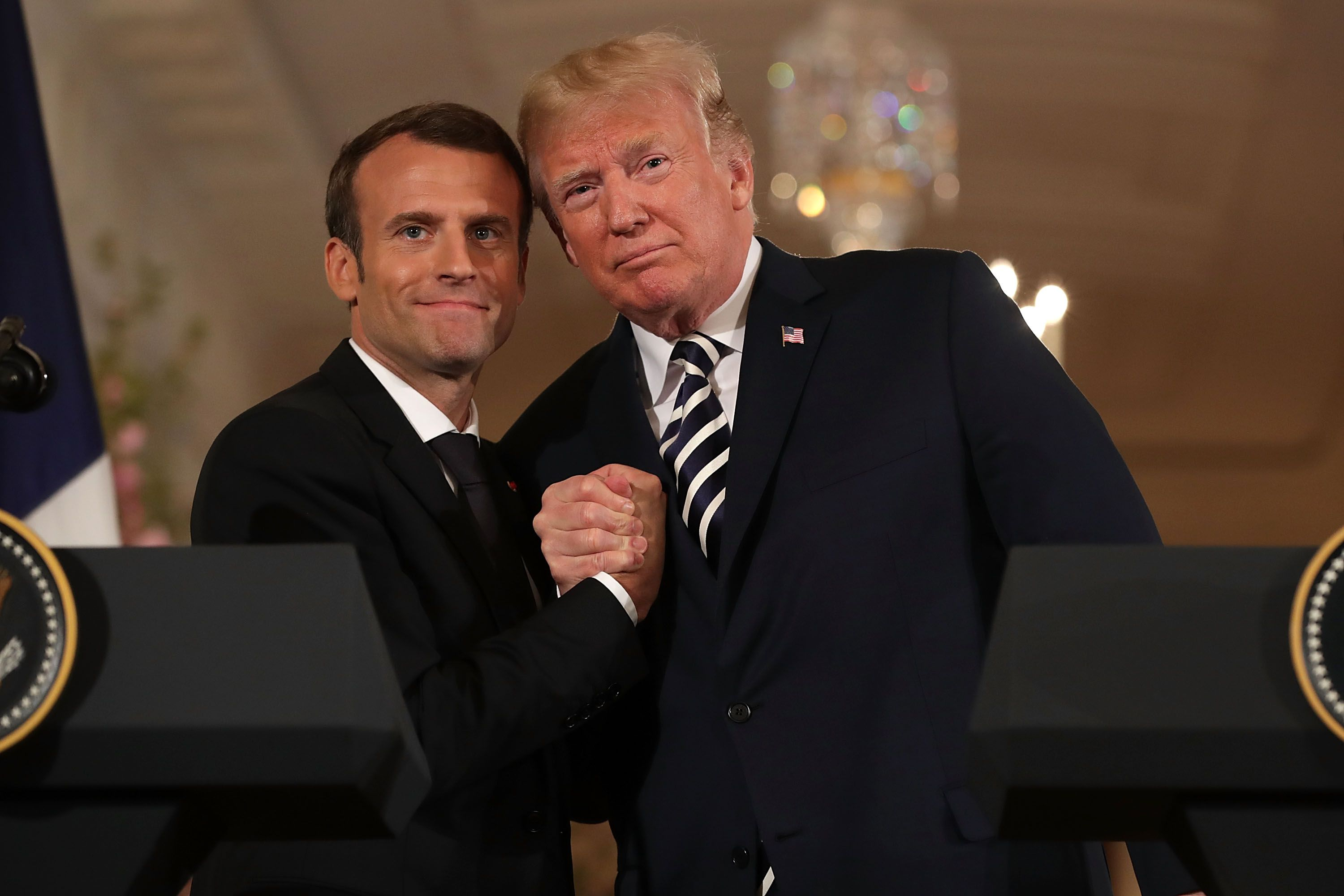 Macron and Trump clasp hands tightly