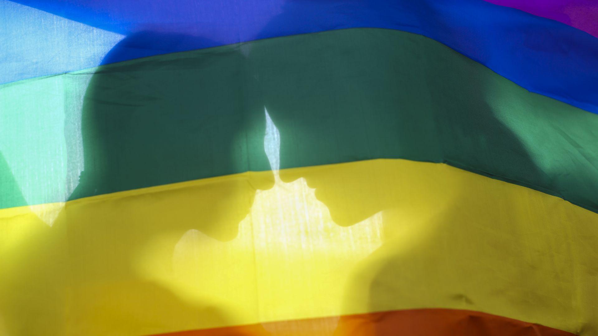 A lesbian couple behind a gay pride flag.