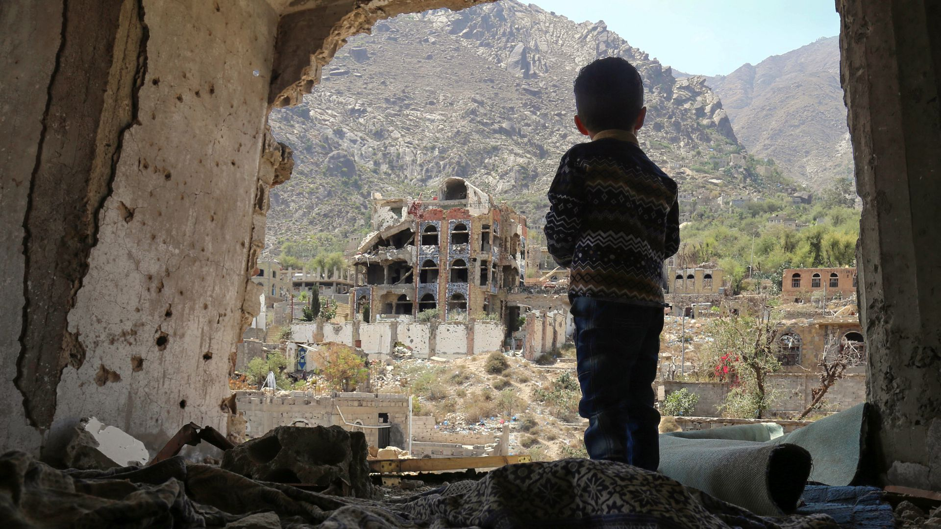A child in Yemen looking at destroyed buildings.