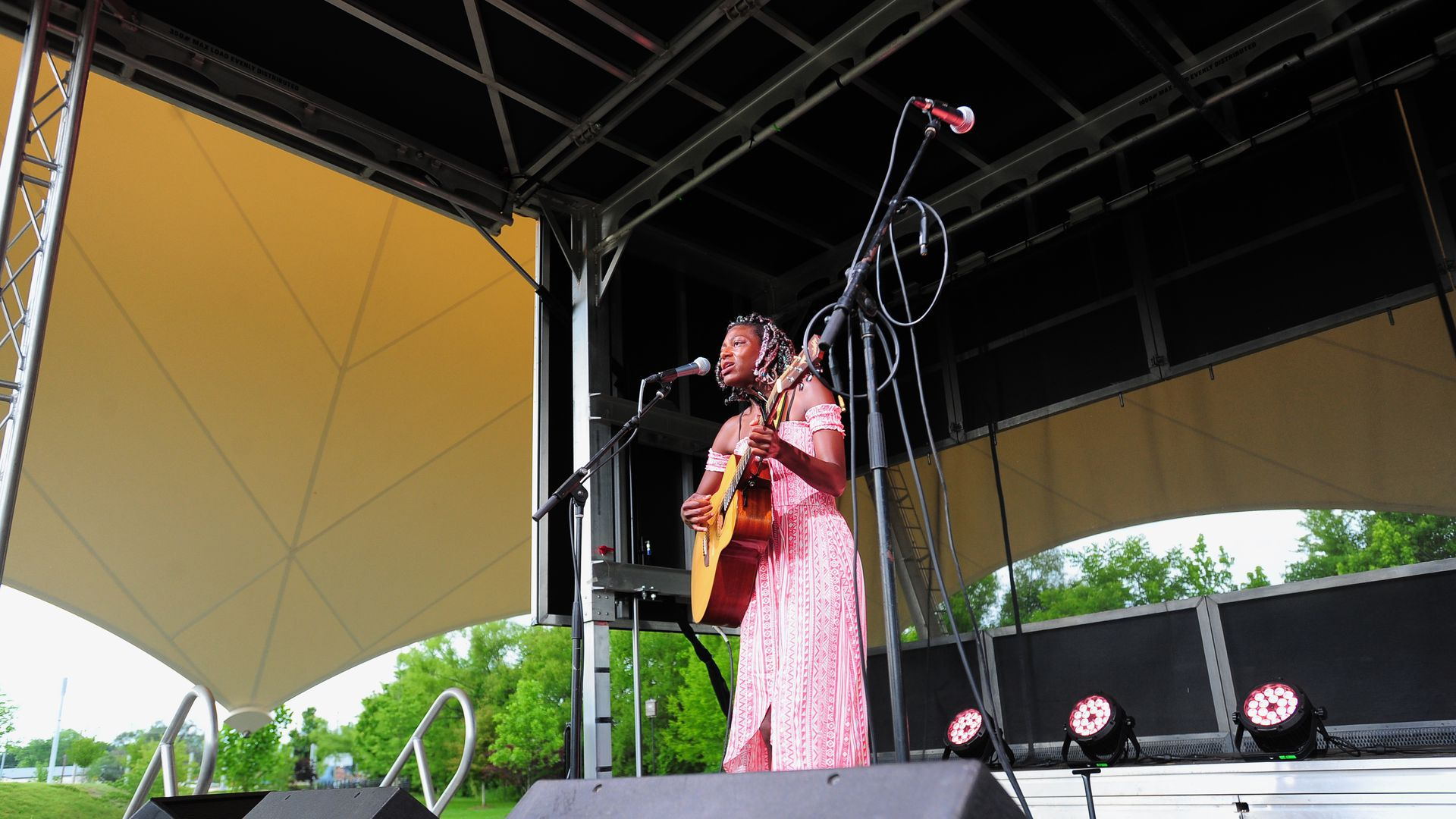 A woman stands on stage playing guitar and singing into a microphone