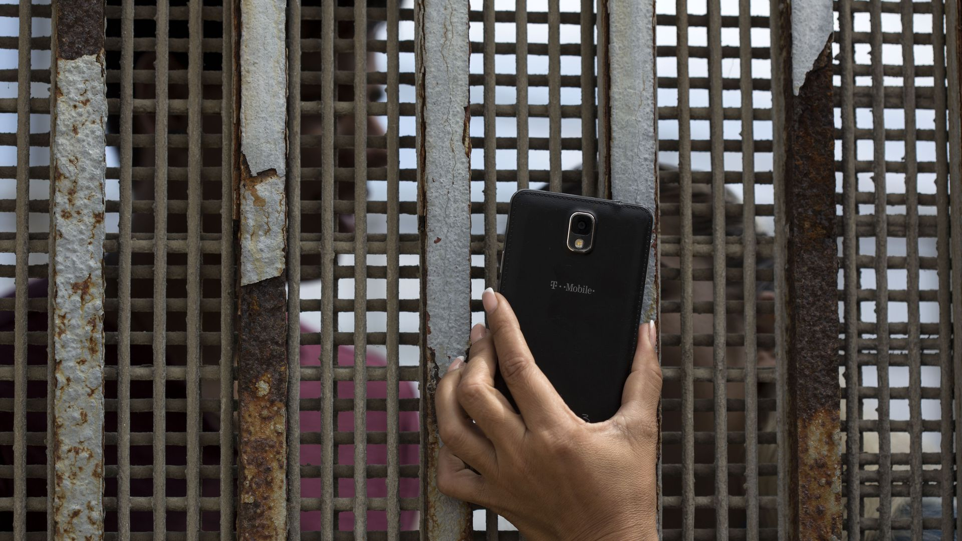 A hand holds a phone up to a grated border wall.