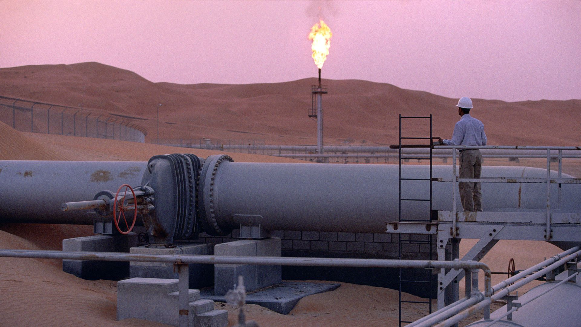 Photo of Saudi Aramco oil field with pink sunset behind it