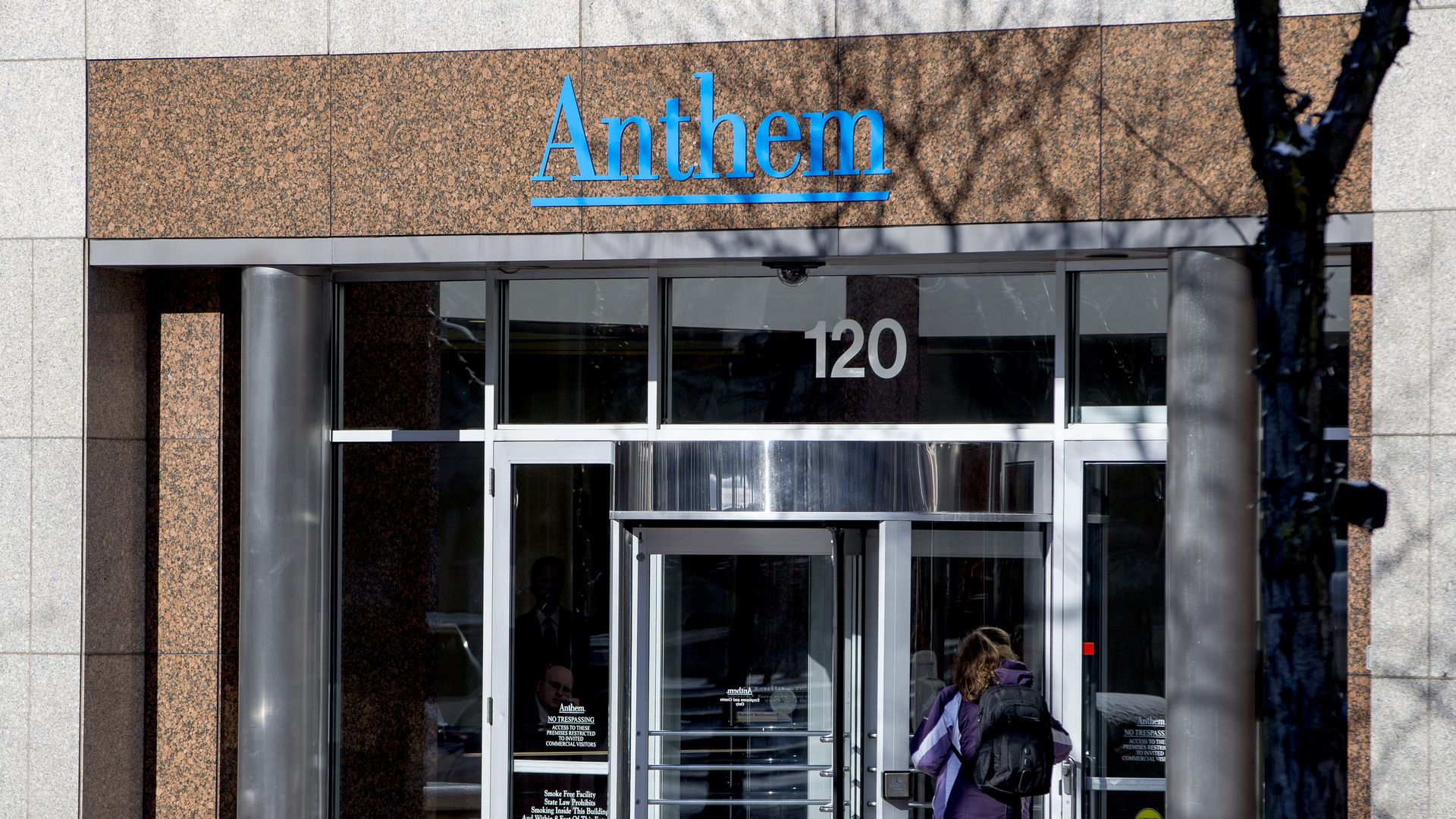In this image, a woman wearing a backpack walks through the front glass doors of an Anthem Blue Cross Blue Shield building.