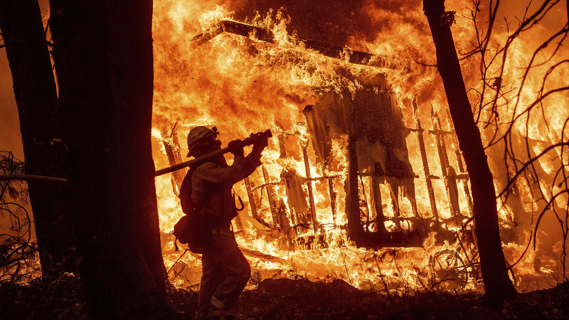 A firefighter attempts to battle a raging California wildfire