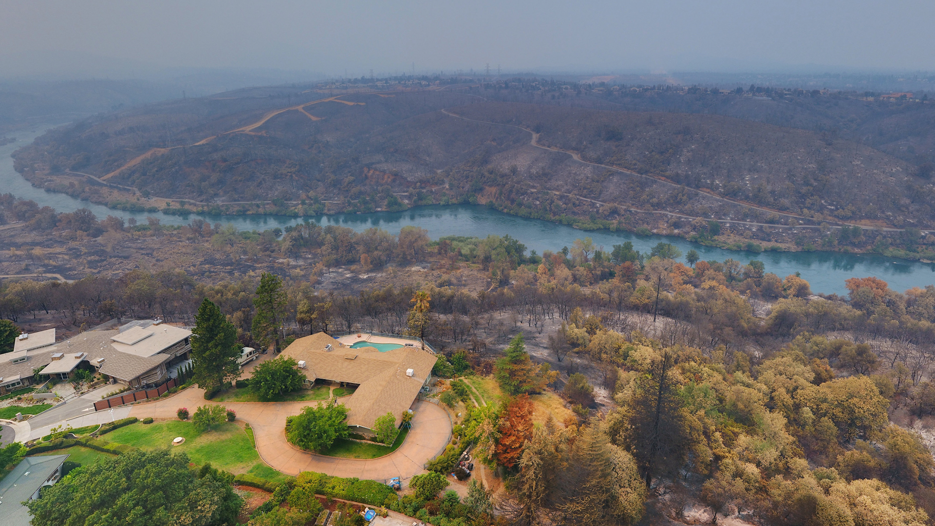 Homes left standing next to charred ground from the Carr Fire in California.