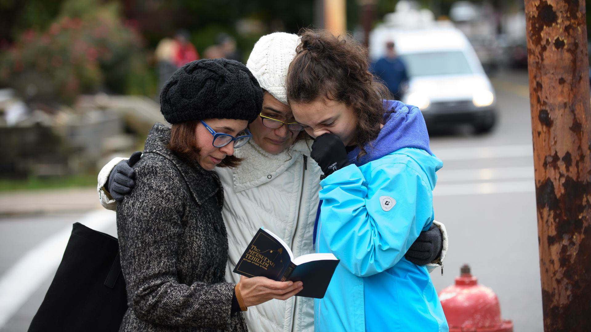 Three women praying from a prayer book at the shooting scene.