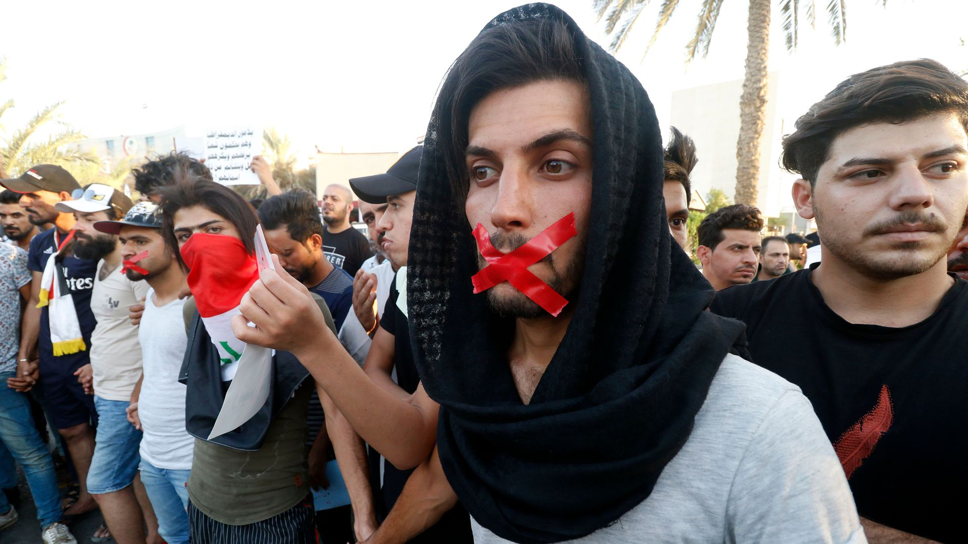 Iraqis with tape on their mouths attend a protest in the southern city of Basra on August 24, 2018.