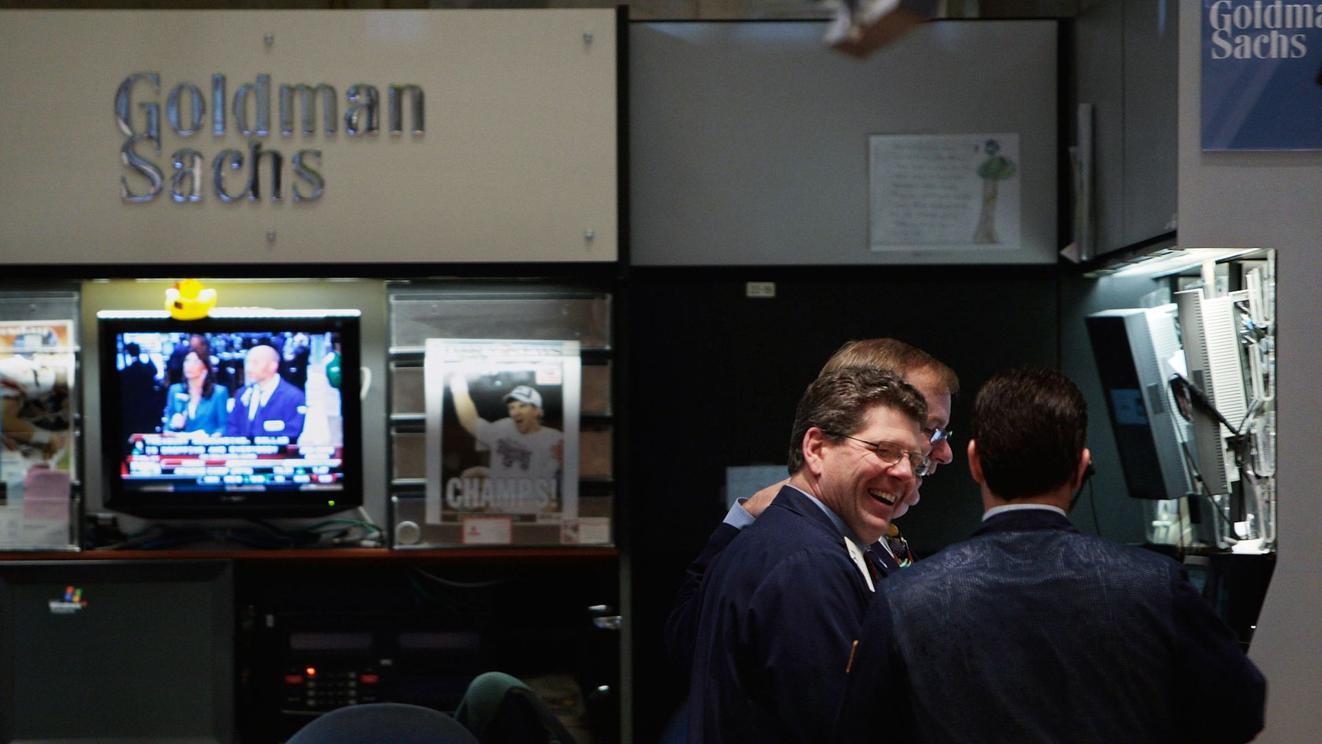 In this image, two men laugh in the Goldman Sachs booth at the New York Stock Exchange.