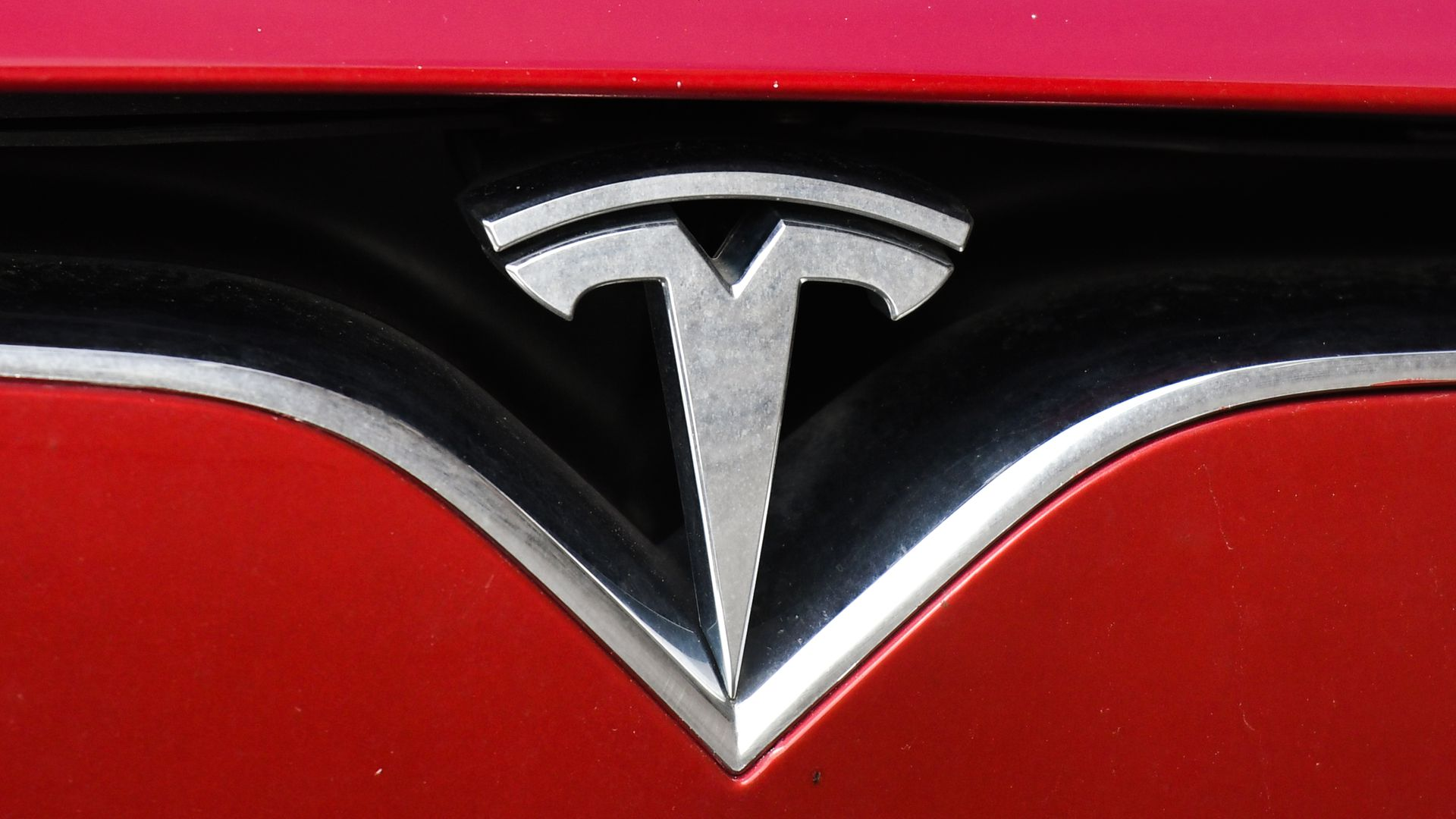 Close-up photo of Tesla logo on a red car.