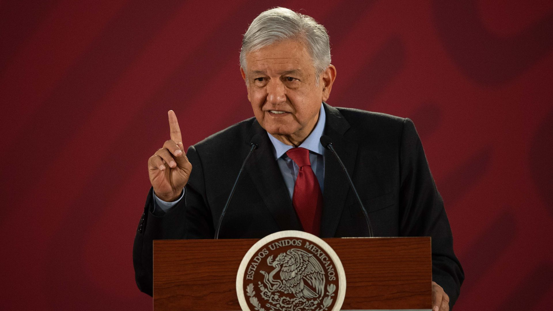 In this image, the Mexican president stands and speaks behind a podium.