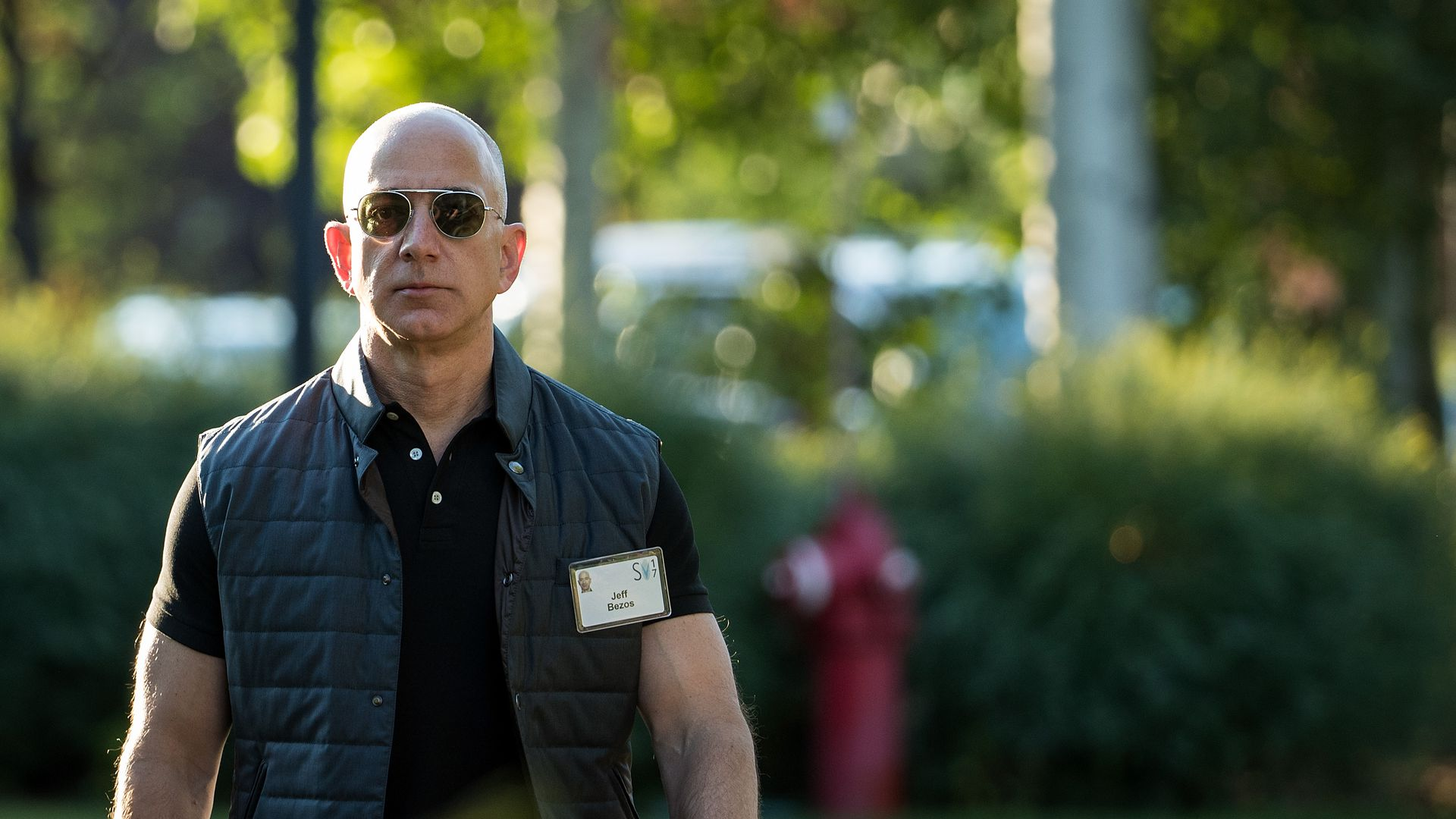 Amazon founder Jeff Bezos walks outside in a short-sleeved polo shirt and vest