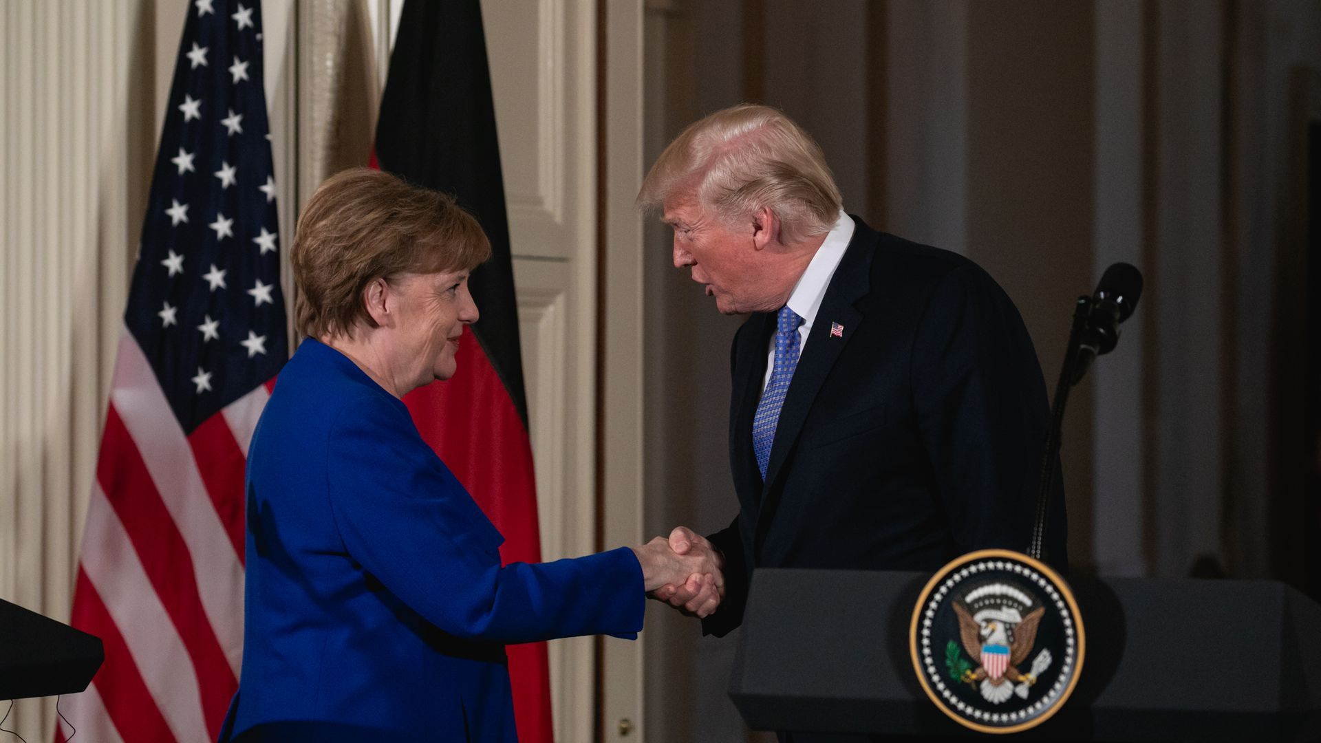 Donald Trump shakes German Chancellor Angela Merkel's hand during a meeting in Washington