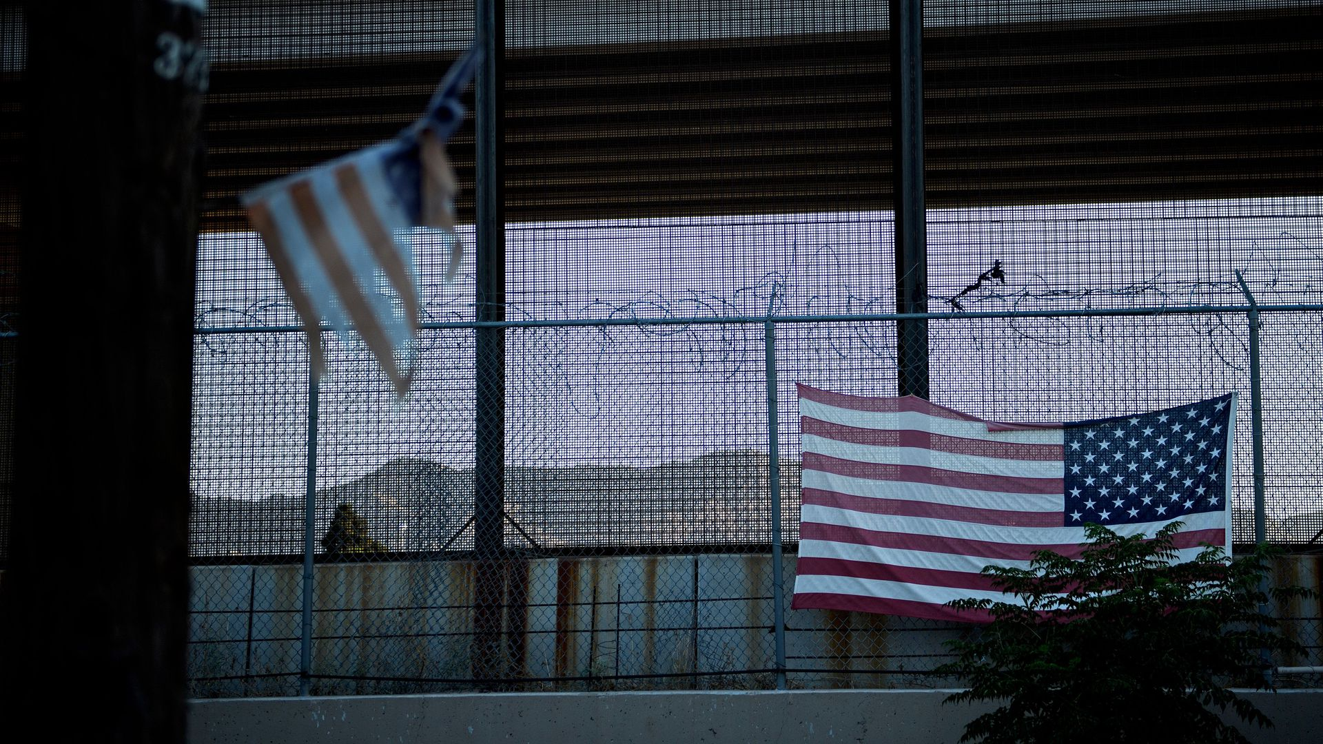 A U.S. flag hanging on a chain-link fence.