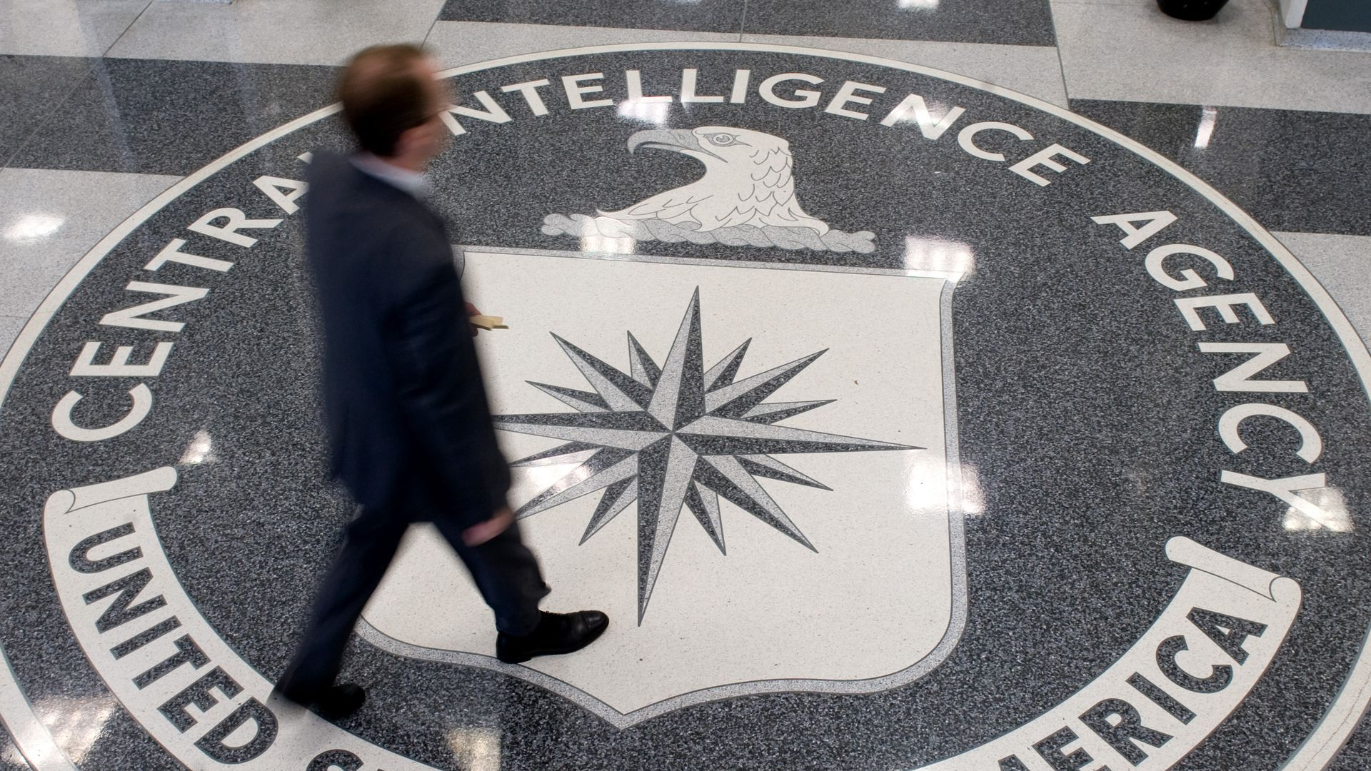 A man crosses the CIA seal in the agency's headquarters